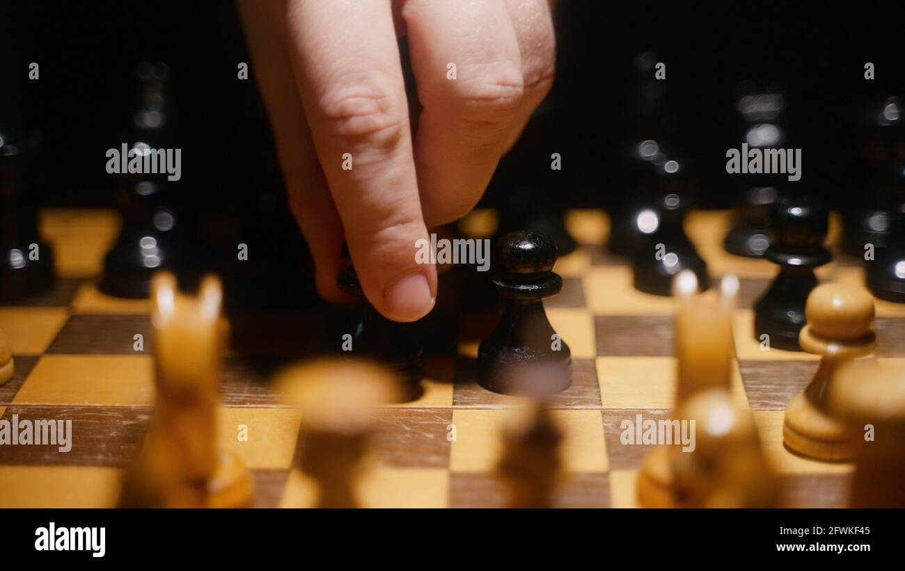 Person uses pawn on the board in chess game. Stock Photo