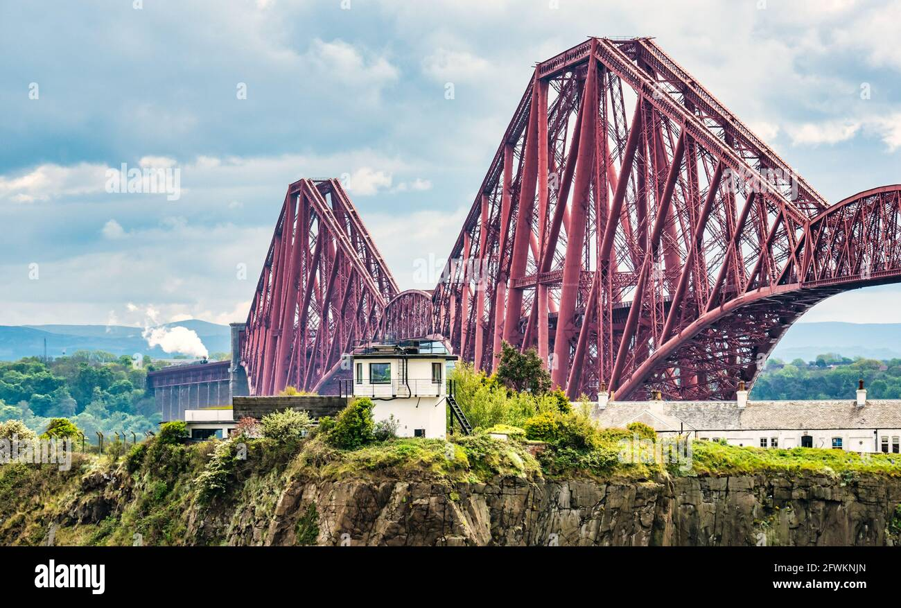 Flying Scotsman steam train crossing the iconic Forth Rail Bridge on its way towards Fife seen from North Queensferry, Scotland, UK Stock Photo