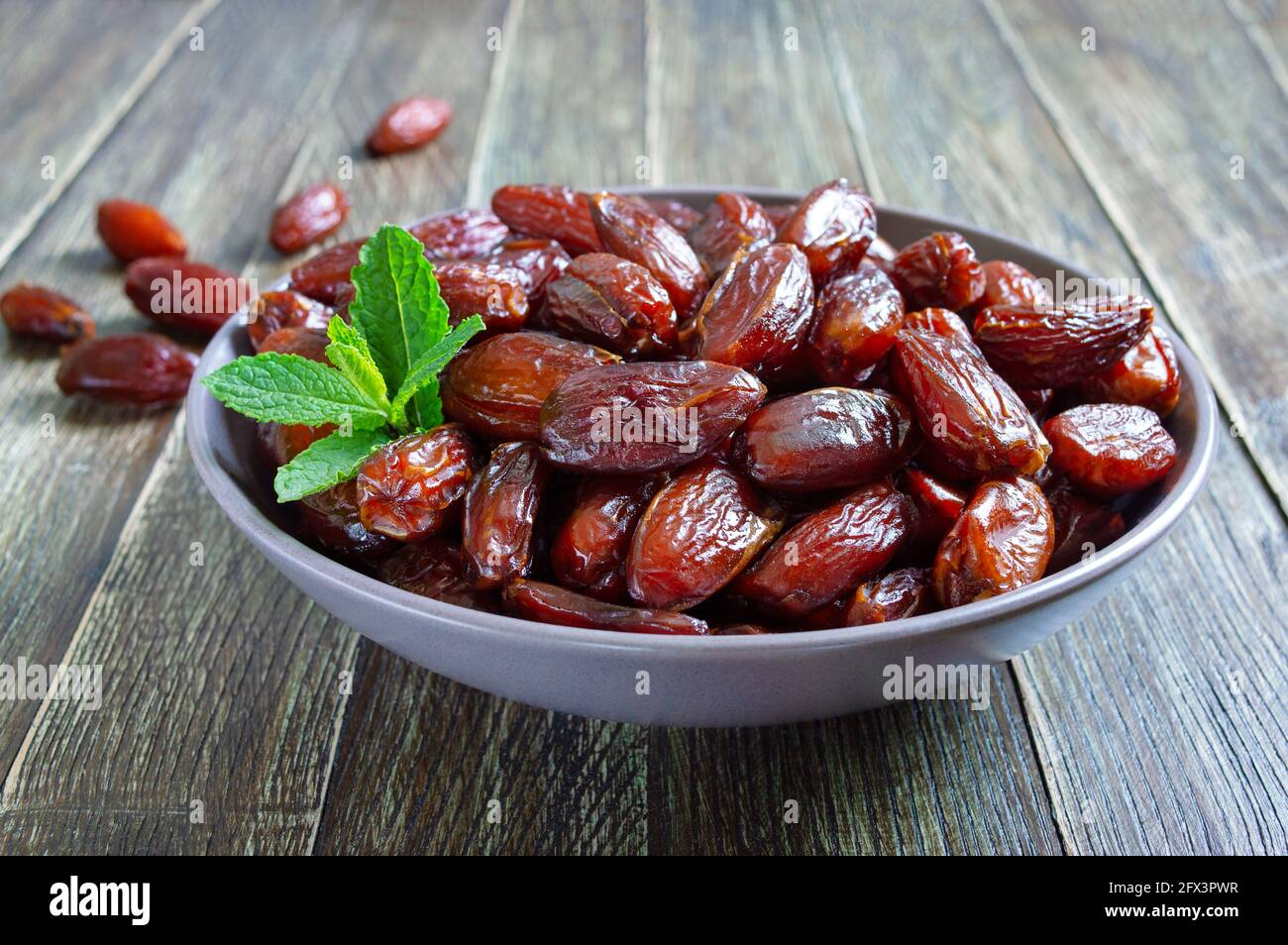 Sun-dried dates in a ceramic bowl and fruits scattered on a wooden table. Organic dried fruits. Stock Photo