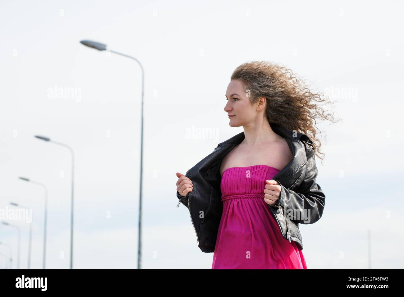 caucasian curly-haired woman in a black leather jacket and a pink dress against the background of a cloudy sky and pillars with lanterns Stock Photo
