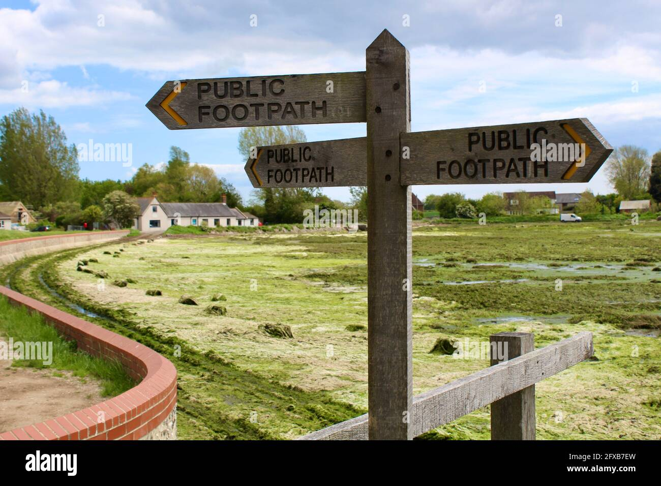 Public footpath sign at Bosham harbour with the old school house in the background. High tide left much seaweed on the road. Car tracks visible. Stock Photo