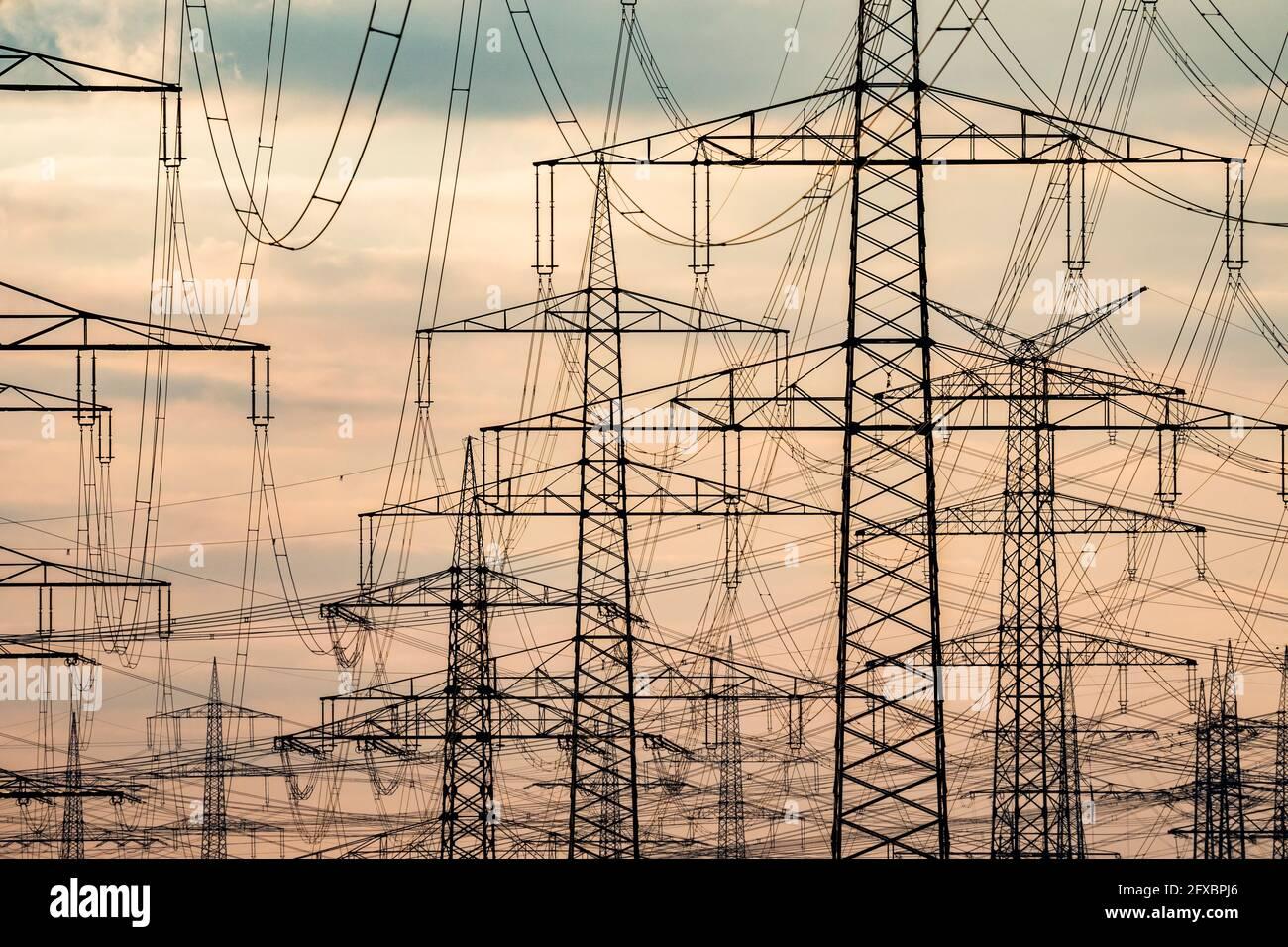 Strommasten, Stromtrasse bei Sonnenuntergang, Niederaußem, Nordrhein-Westfalen, Deutschland Stock Photo
