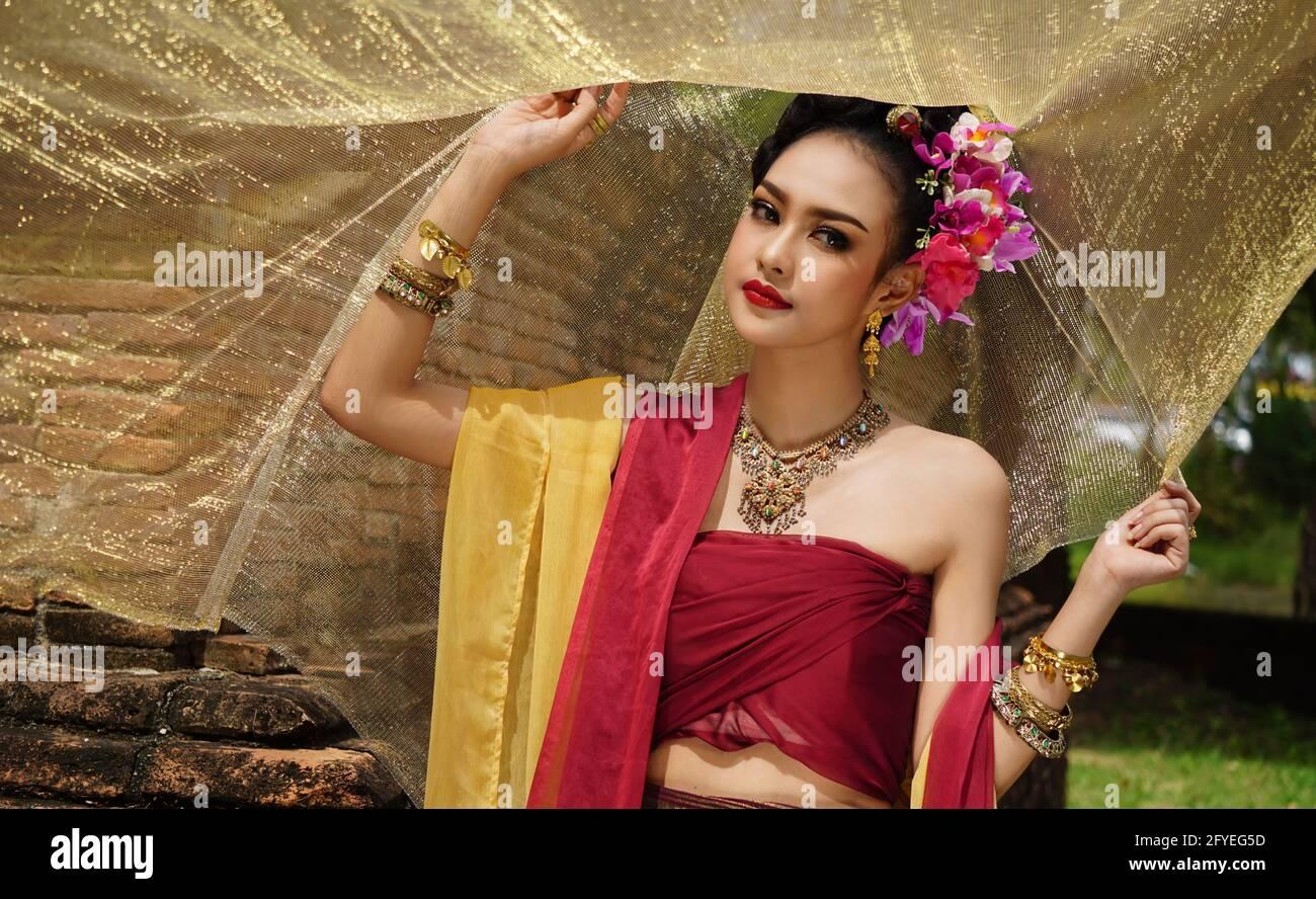 https://c8.alamy.com/comp/2FYEG5D/beautiful-woman-thai-national-costume-traditional-thai-dress-thai-woman-good-mood-beautiful-smile-background-image-with-noise-and-grain-2FYEG5D.jpg