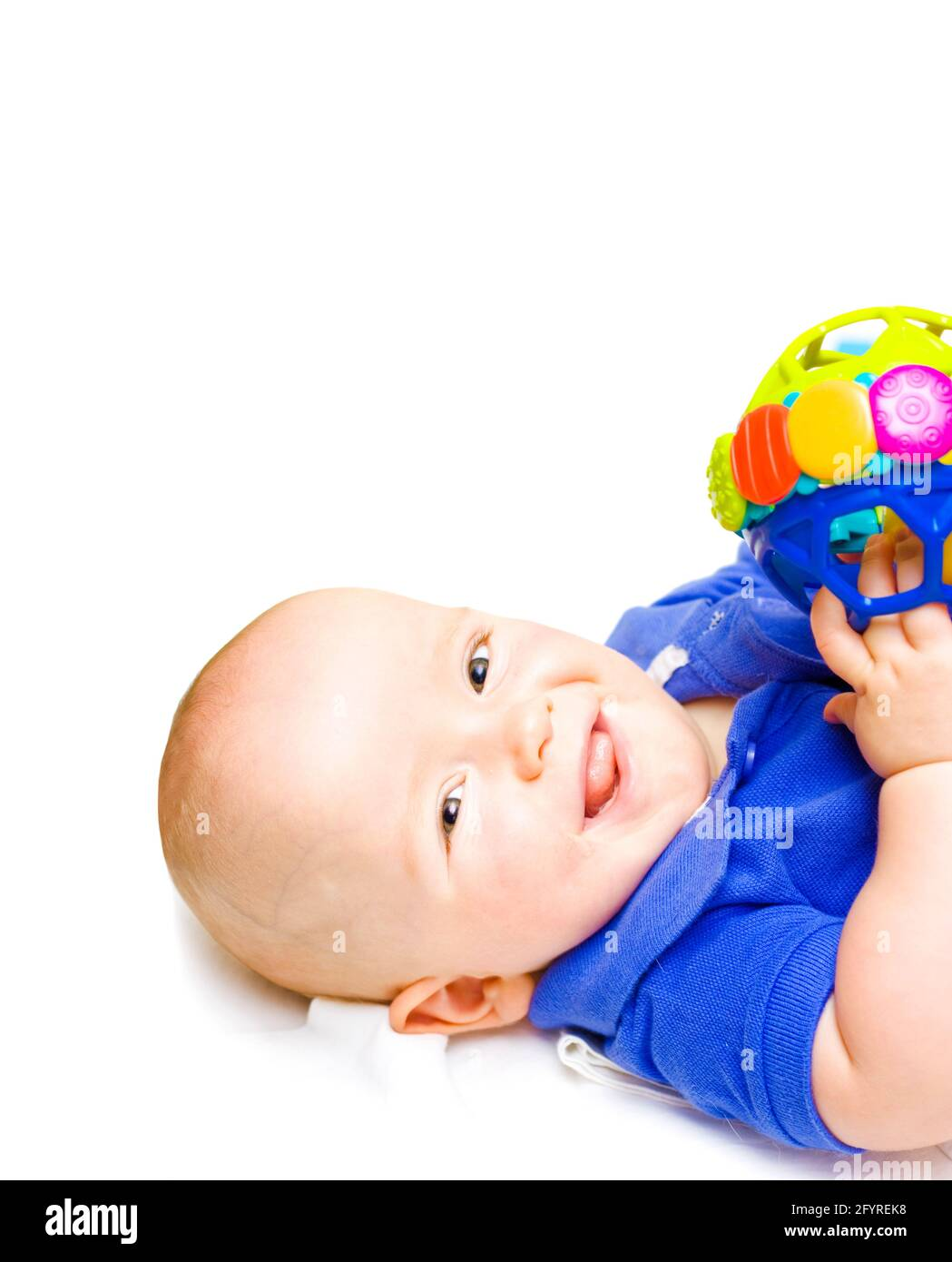 Gurgling Happy Baby With Toy, baby lying on his back witha contented happy expression while playing with a colourful toy, studio close-up on white Stock Photo