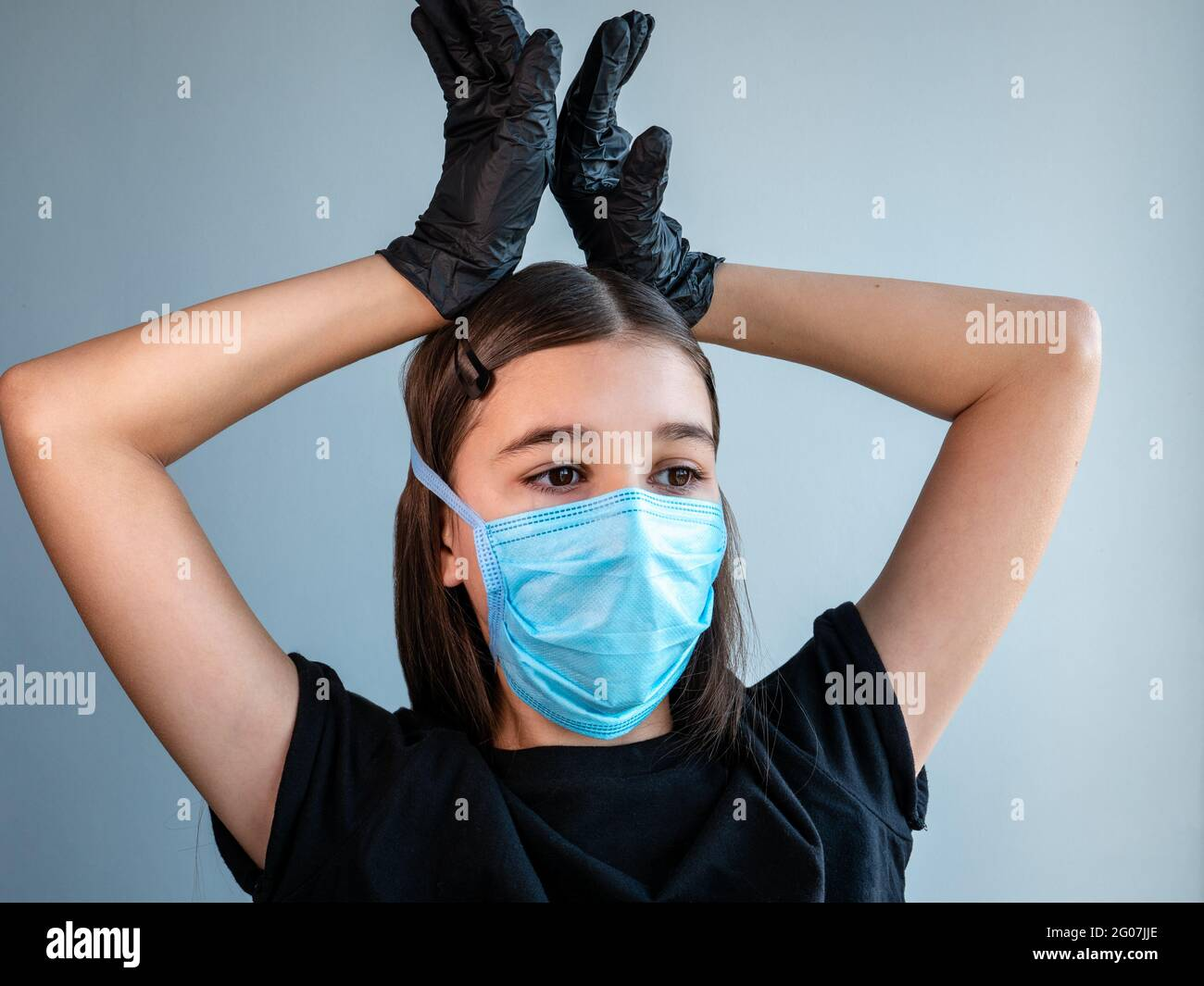 Female teenage girl in a blue protective medical face mask shows corona by holding her hands in black latex gloves above her head. Coronavirus concept Stock Photo