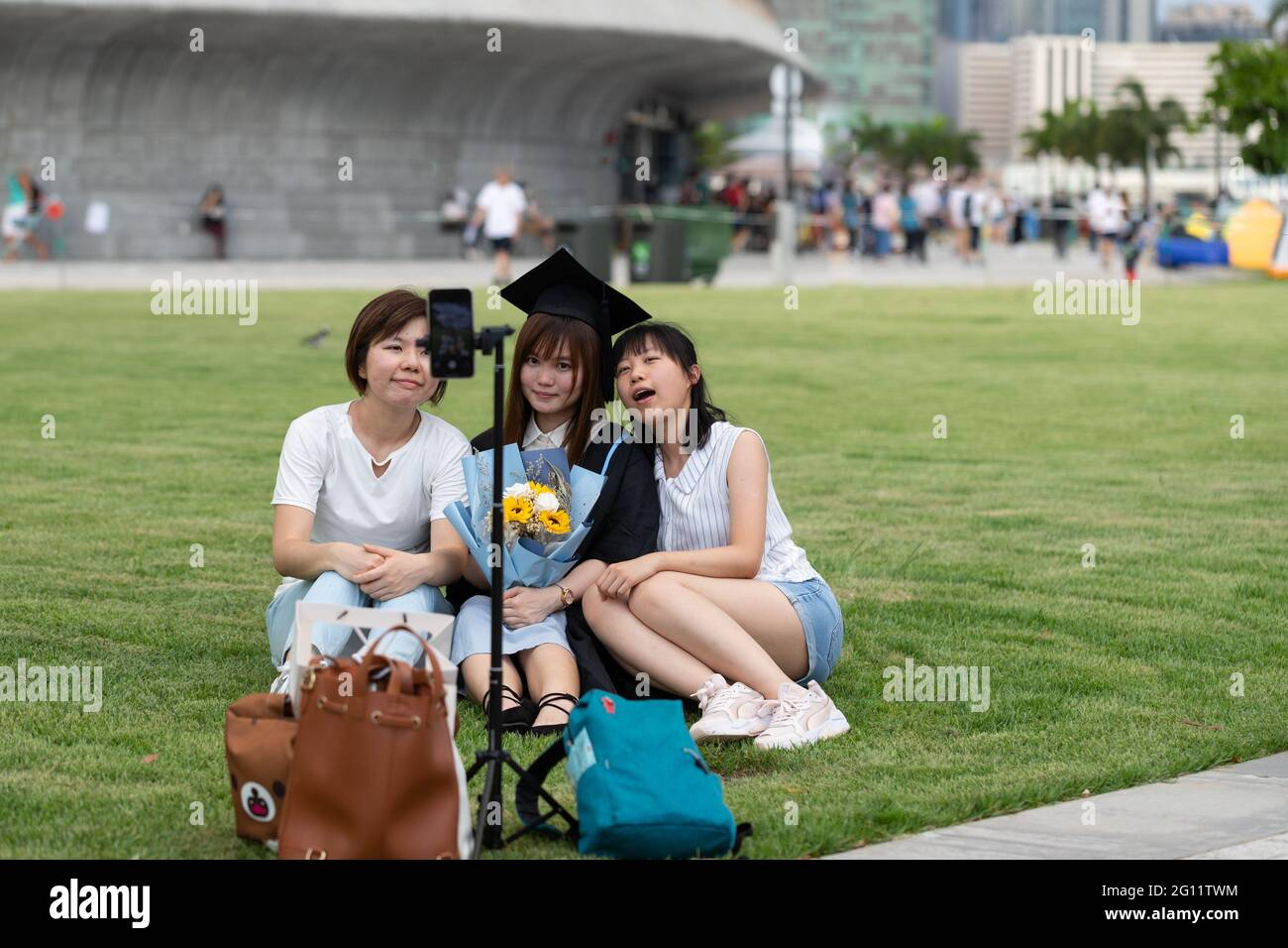 19 5 2021 happy freshly graduated undergraduate and friends in Academic dress gown sit on grass field near West Kowloon Waterfront Promenade, Hong Kon Stock Photo