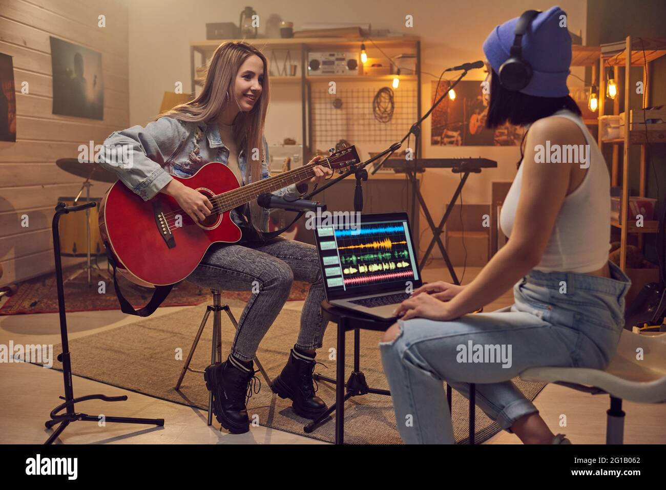 Two young women recording new music in front of laptop Stock Photo