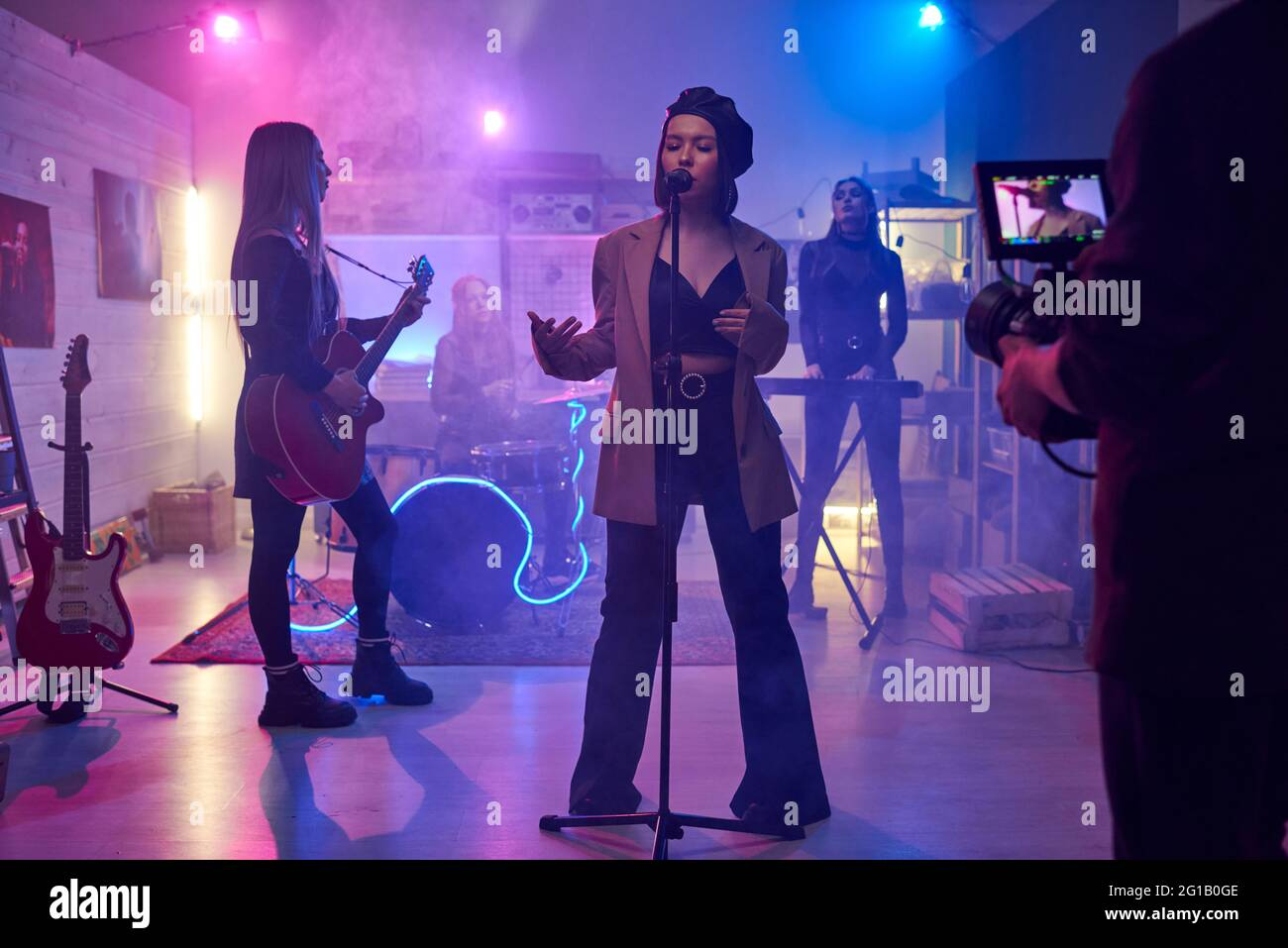 Young female singing on stage in front of cameraman shooting music video Stock Photo