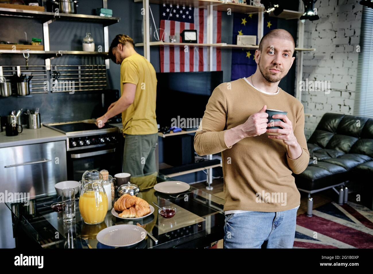 Young man with mug standing by table against another guy Stock Photo