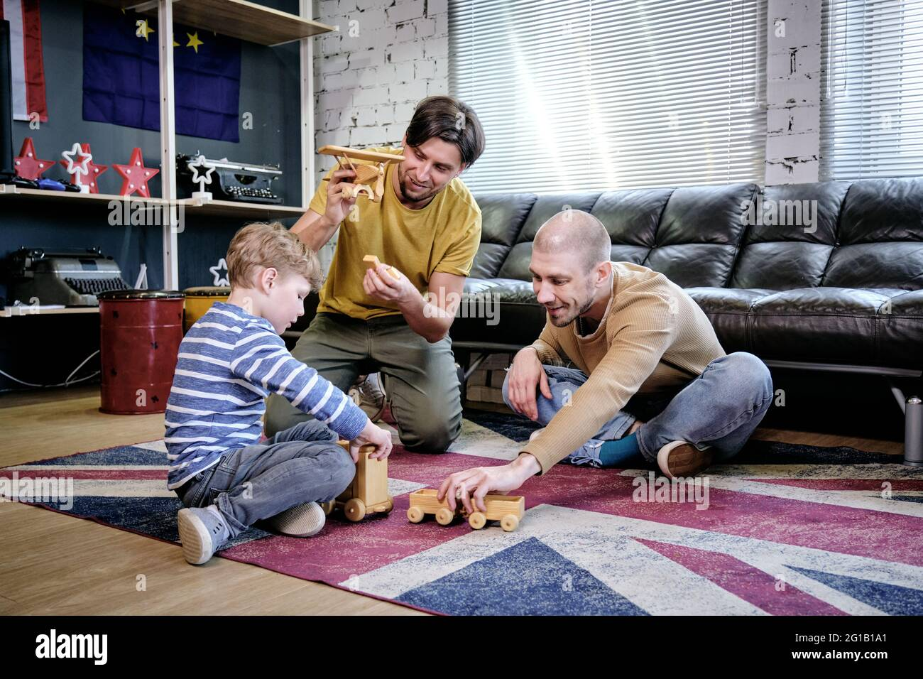 Two young men and little boy playing on the floor of living-room Stock Photo