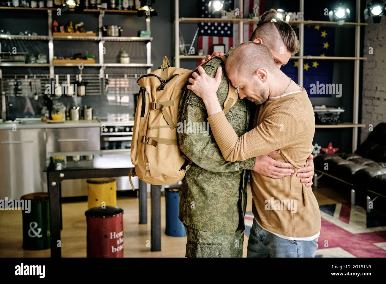 Two young gay men standing in embrace in front of camera Stock Photo