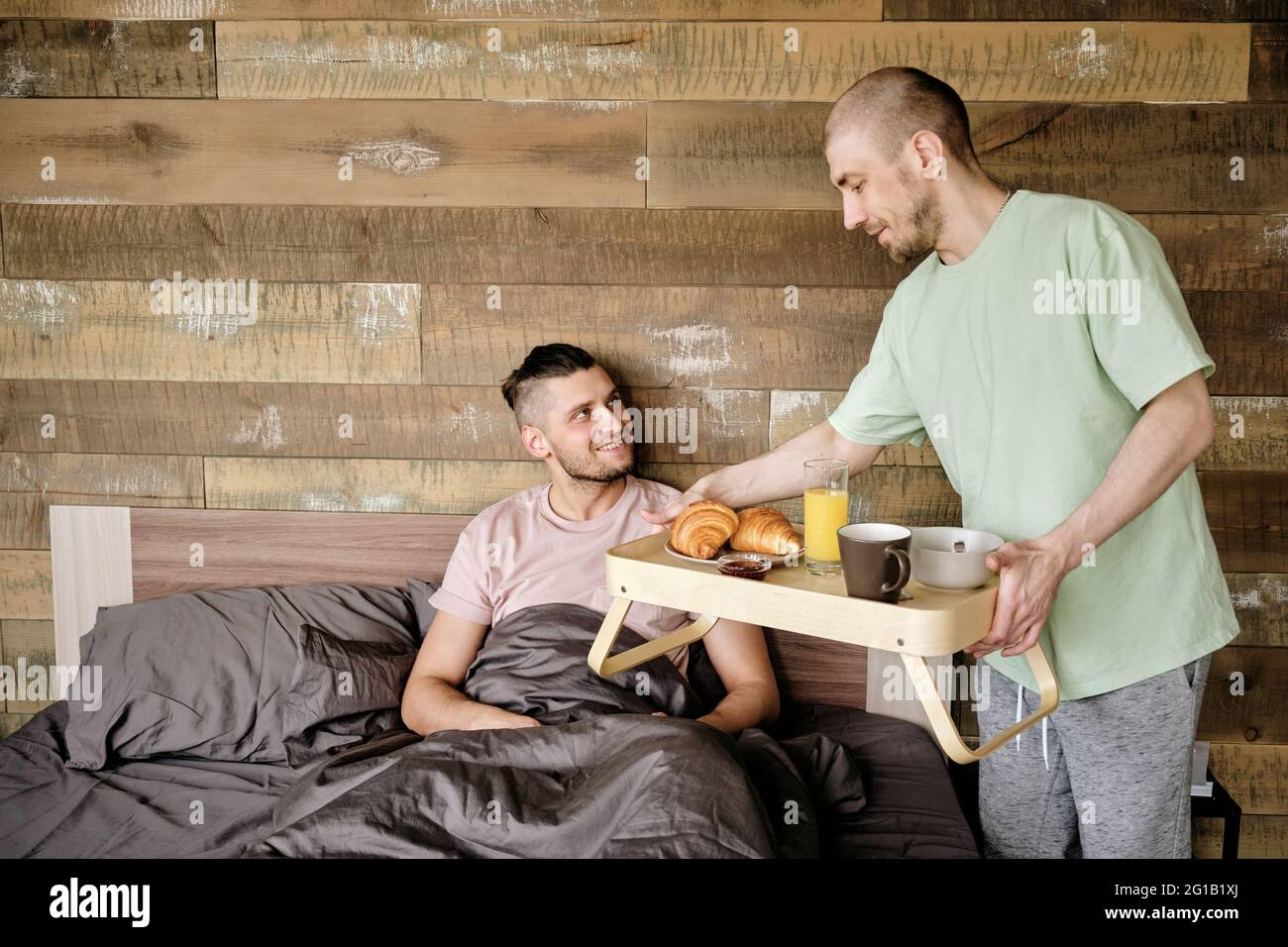 Young man bringing small table with breakfast for his boyfriend in bed Stock Photo