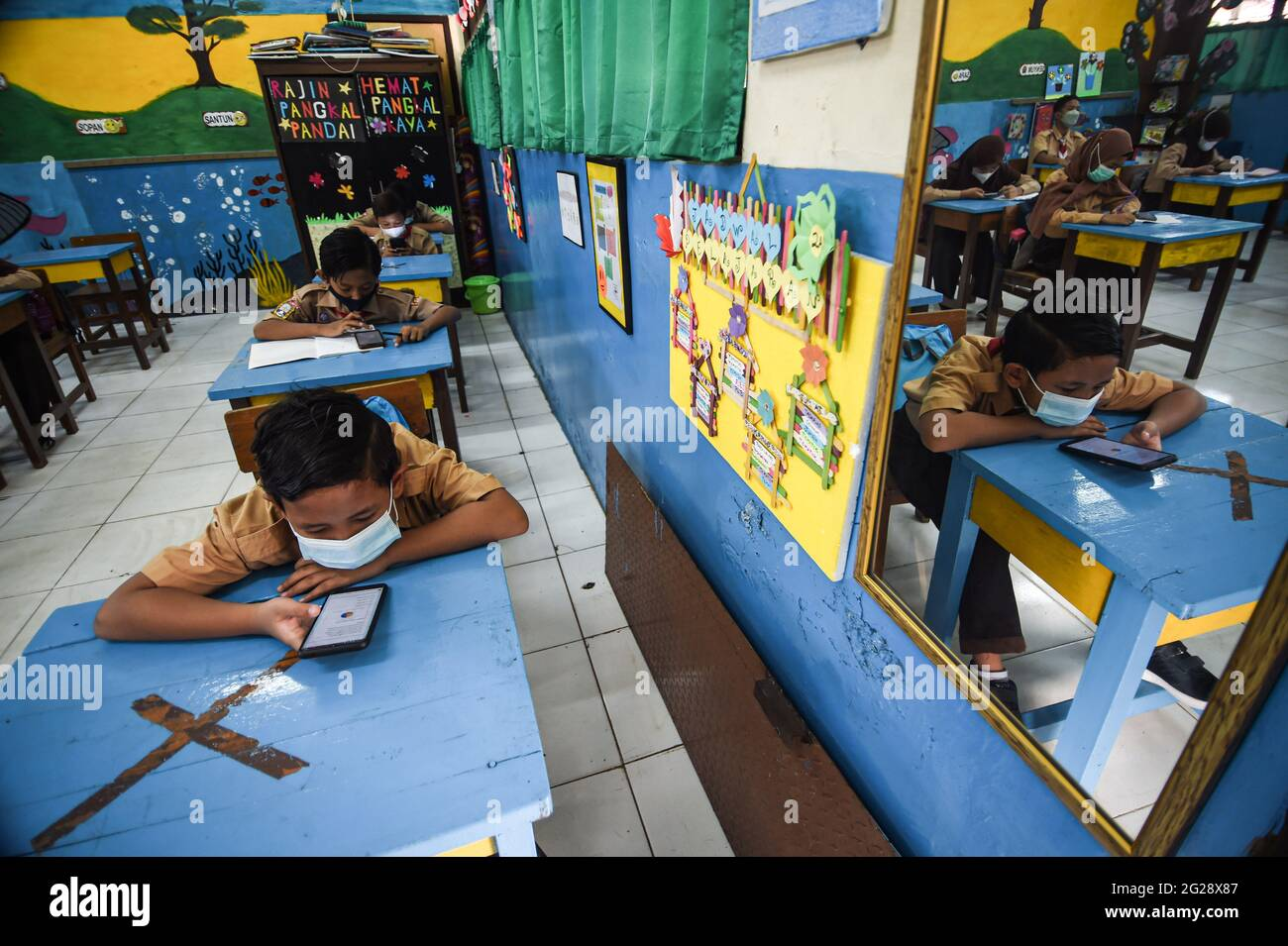 Jakarta, Indonesia. 9th June, 2021. Elementary students wearing face masks are seen in a classroom during a trial face-to-face learning activity amid the COVID-19 outbreak at a school in Jakarta, Indonesia, June 9, 2021. Credit: Agung Kuncahya B./Xinhua/Alamy Live News Stock Photo