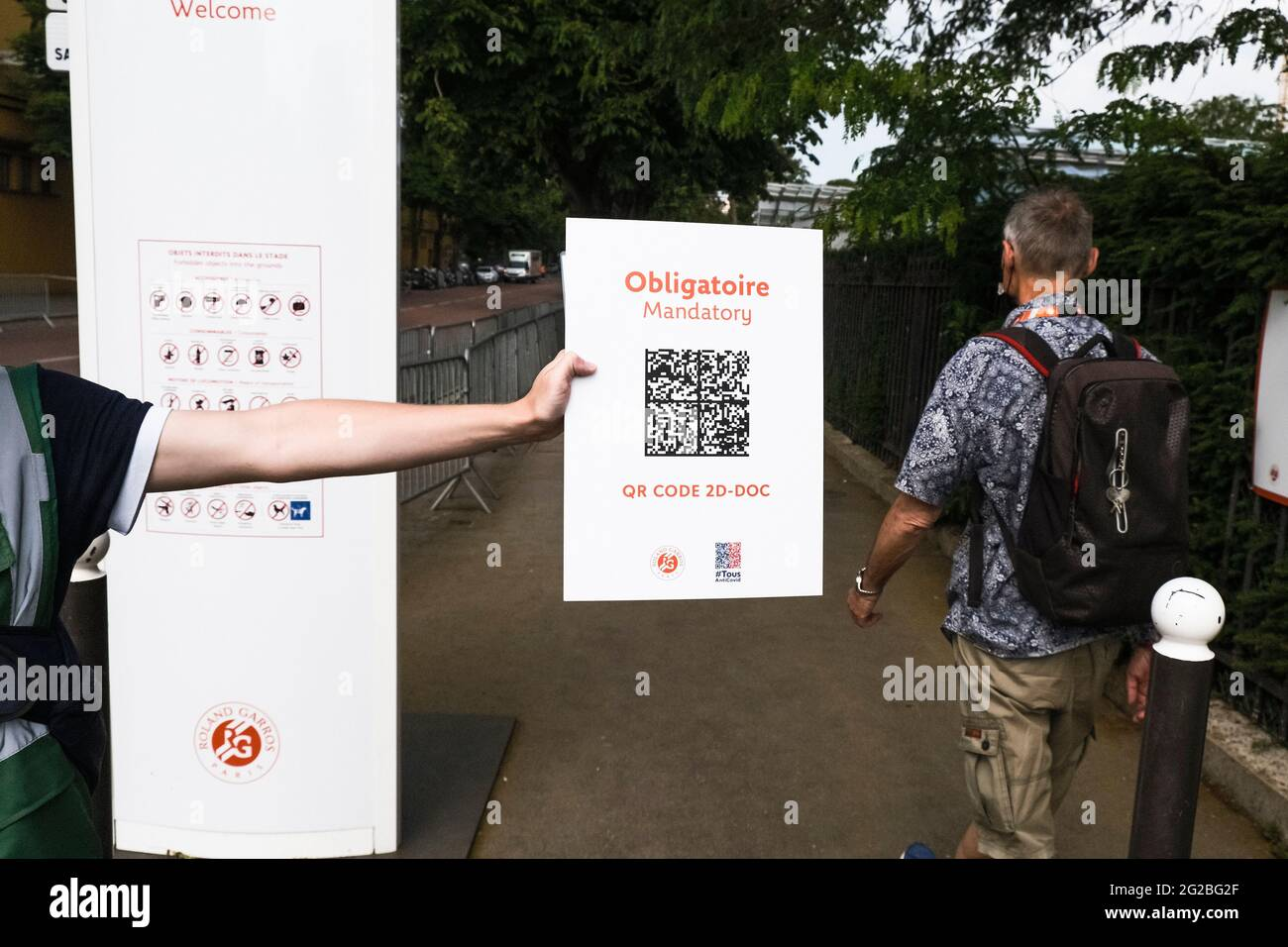 Paris, France. 10th June, 2021. Tennis: Grand Slam, French Open. An employee holds a sign at the entrance to remind spectators of a valid Corona test or vaccination. By means of a QR code, access to the tournament site is controlled in this way. Since the new Corona rules on June 9, 2021, more people are allowed back into the Stade Roland Garros. As the curfew in Paris now only starts at 11pm, 5000 spectators will also be allowed onto Centre Court. Credit: Frank Molter/dpa/Alamy Live News Stock Photo