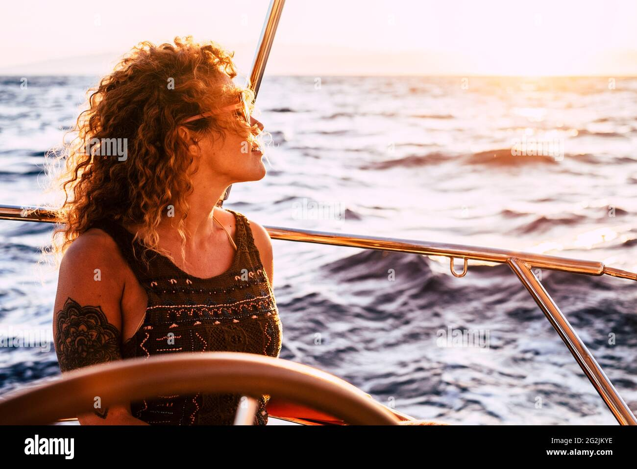 Adult rich woman enjoy luxury lifestyle traveling on sailboat yacht for summer holiday vacation - pretty female people outdoor freedom with ocean sea around in the sunset Stock Photo