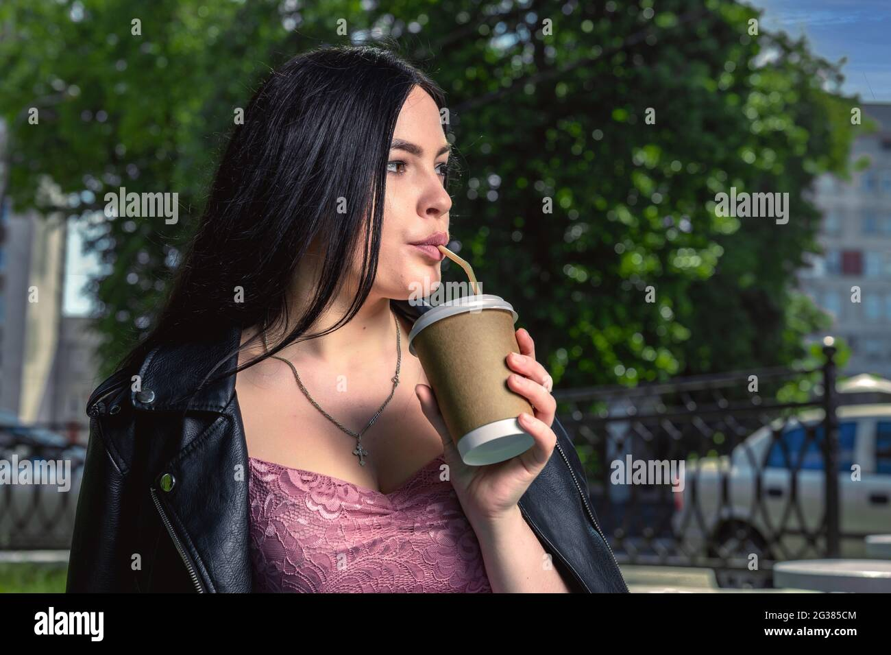 Young woman drinking coffee in the street. Female in the city street drinking a hot beverage. Image of attractive young woman drinking coffee at the t Stock Photo