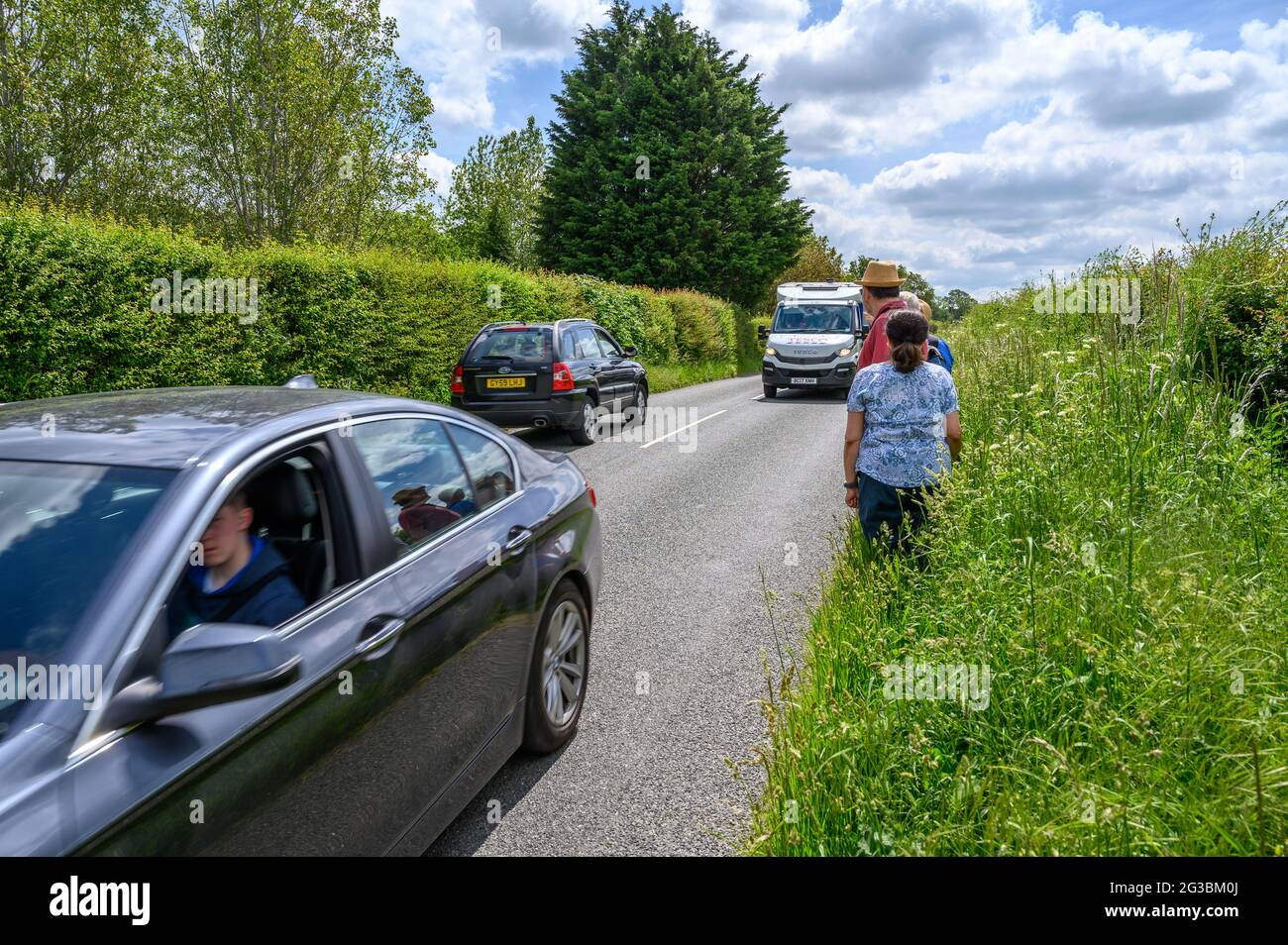 A group of ramblers standing on the grass verge while traffic drives past along South Road between Plumpton Green and South Chailey, East Sussex, Engl Stock Photo