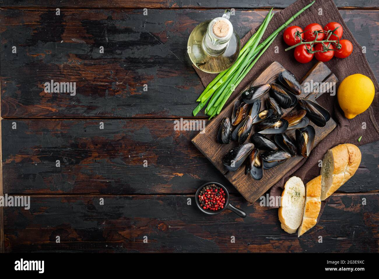 Steamed mussels in white wine set, on wooden cutting board, on old dark wooden table background, top view flat lay , with copyspace and space for text Stock Photo