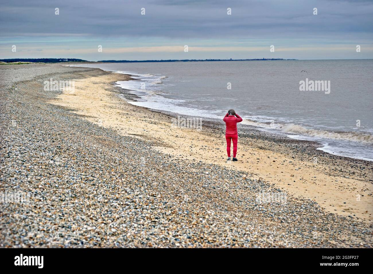woman in red on sizewell beach looking out to sea towards southwold with binoculars suffolk england Stock Photo