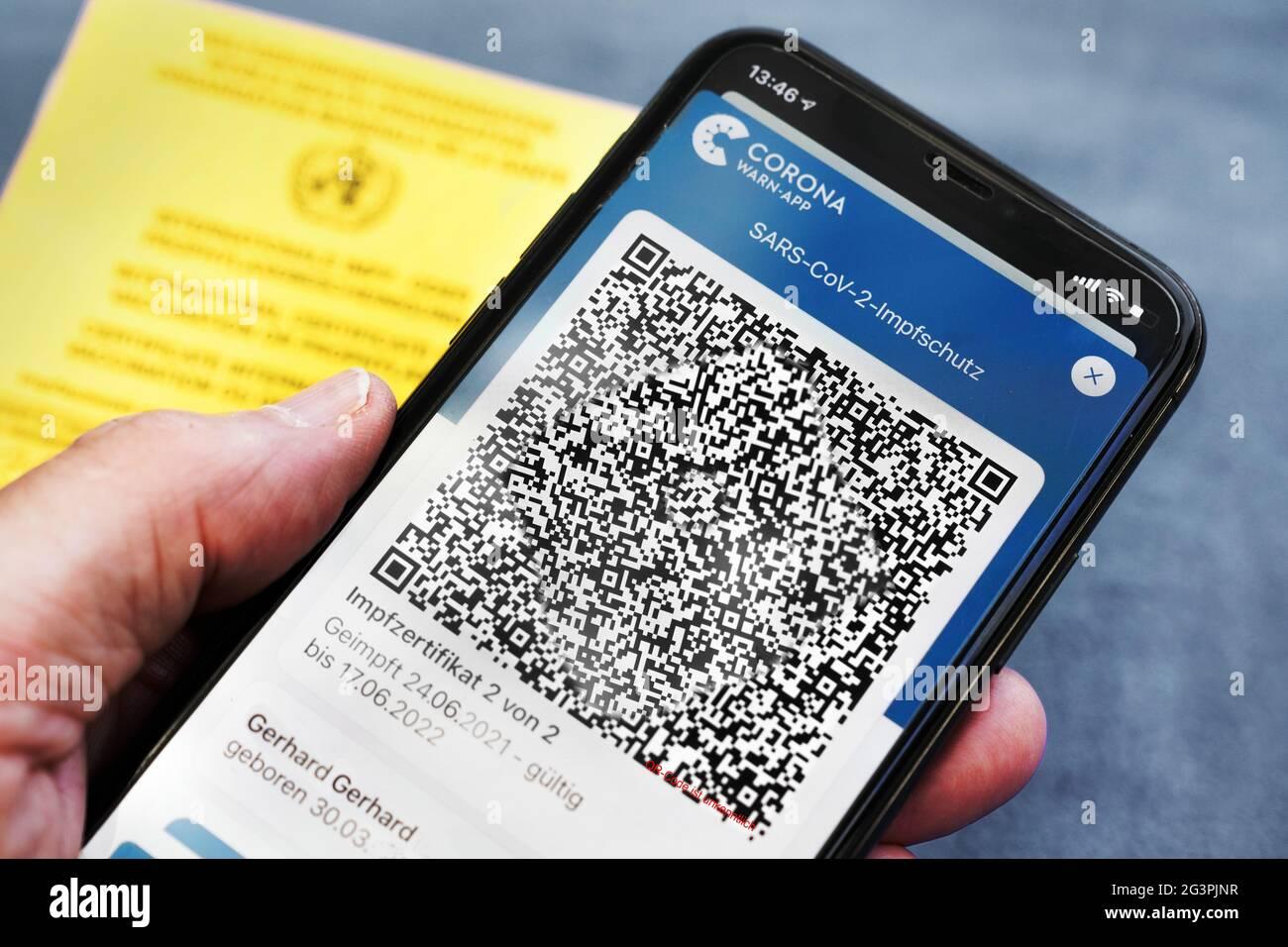QR-Code, das digitale Impfzertifikat in der Corona Warn-App auf einem Smartphone bestätigt eine abgeschlossenen Impfung gegen Covid-19. Liegt auf der gelben Internationalen Impfbescheinigung, Impfpass. - ACHTUNG! QR-Code und persönliche Angaben sind unkenntlich gemacht! Stock Photo