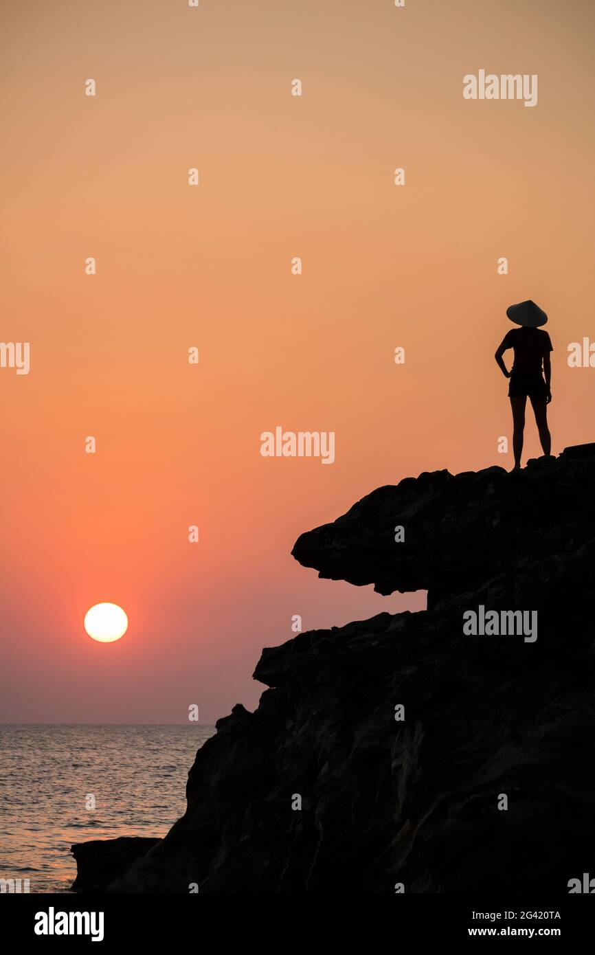 Silhouette of young woman wearing conical hat and looking out to sea from rock ledge next to Dinh Cao Shrine at sunset, Duong Dong, Phu Quoc Island, K Stock Photo