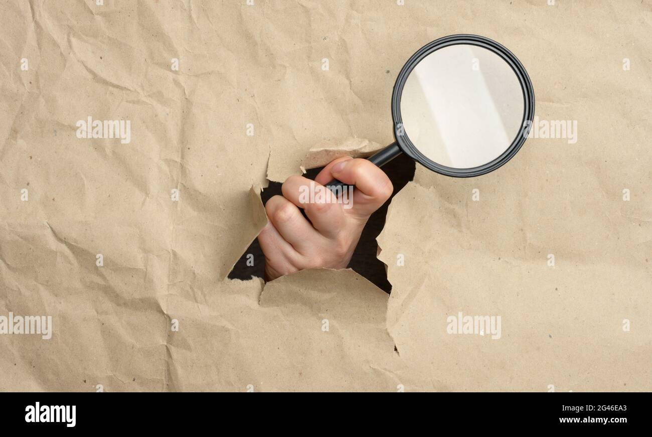 A woman's hand holds a glass magnifier, part of the body sticks out of a hole in brown paper Stock Photo