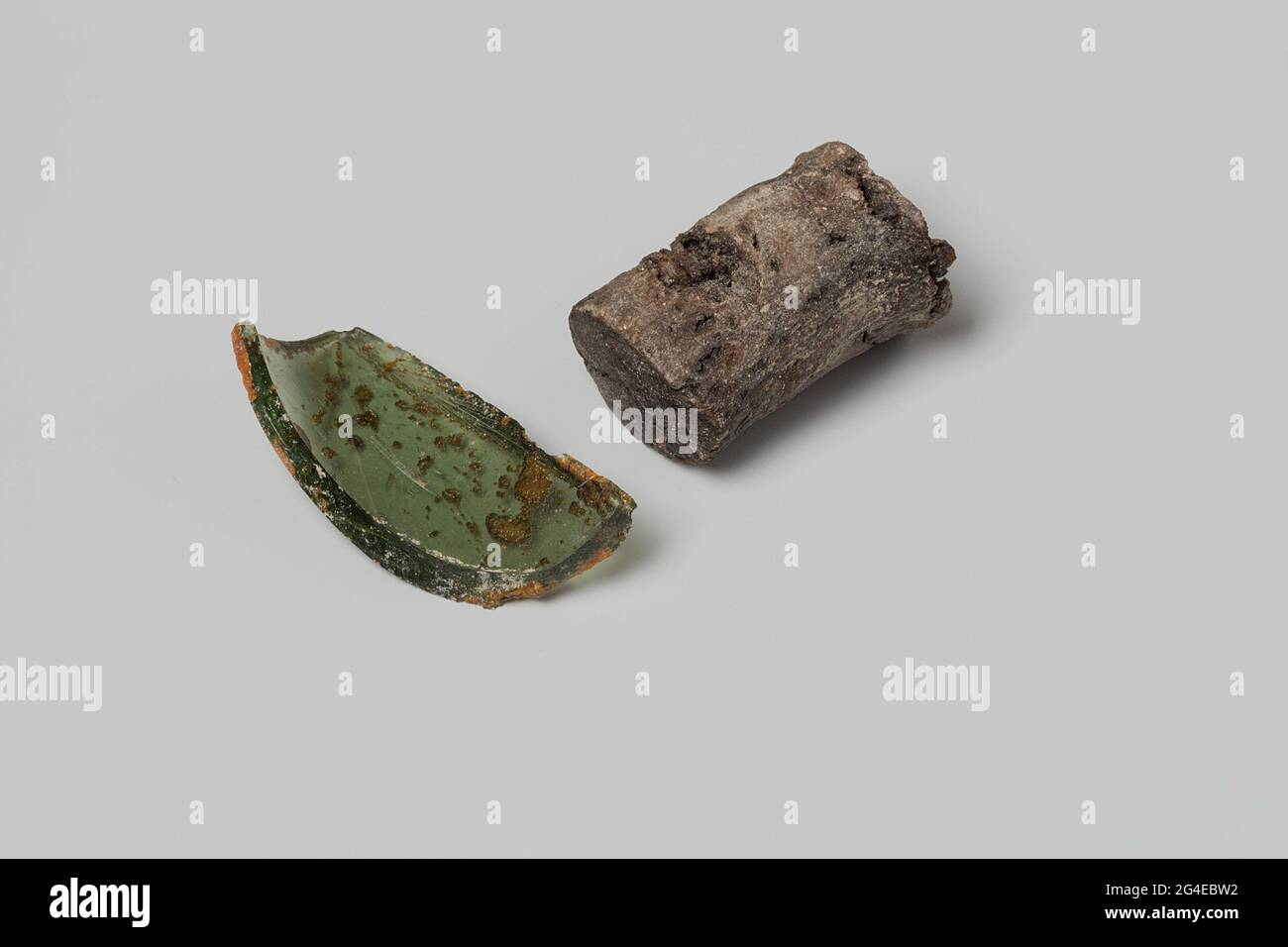 Glass shard and cork from a wine bottle from the wreck of the East Indies Flying Heart. The brown cork and the green glass fragment ever part of a wine bottle. Stock Photo