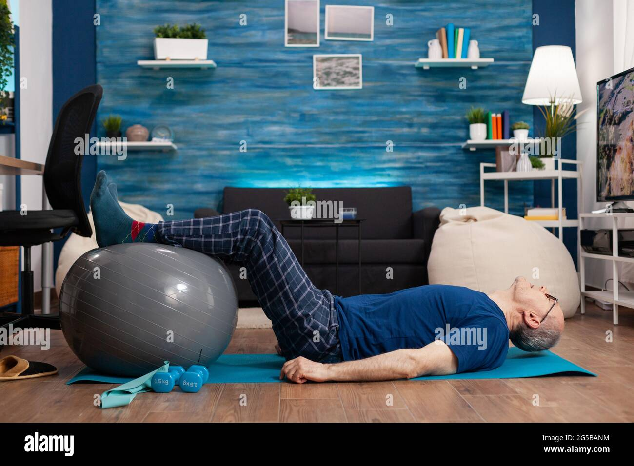 Retired senior sportman sitting on yoga mat practicing warming legs up exercises using swiss ball stretching abdominals muscles. Focused pensioner training body strength resistance in living room Stock Photo