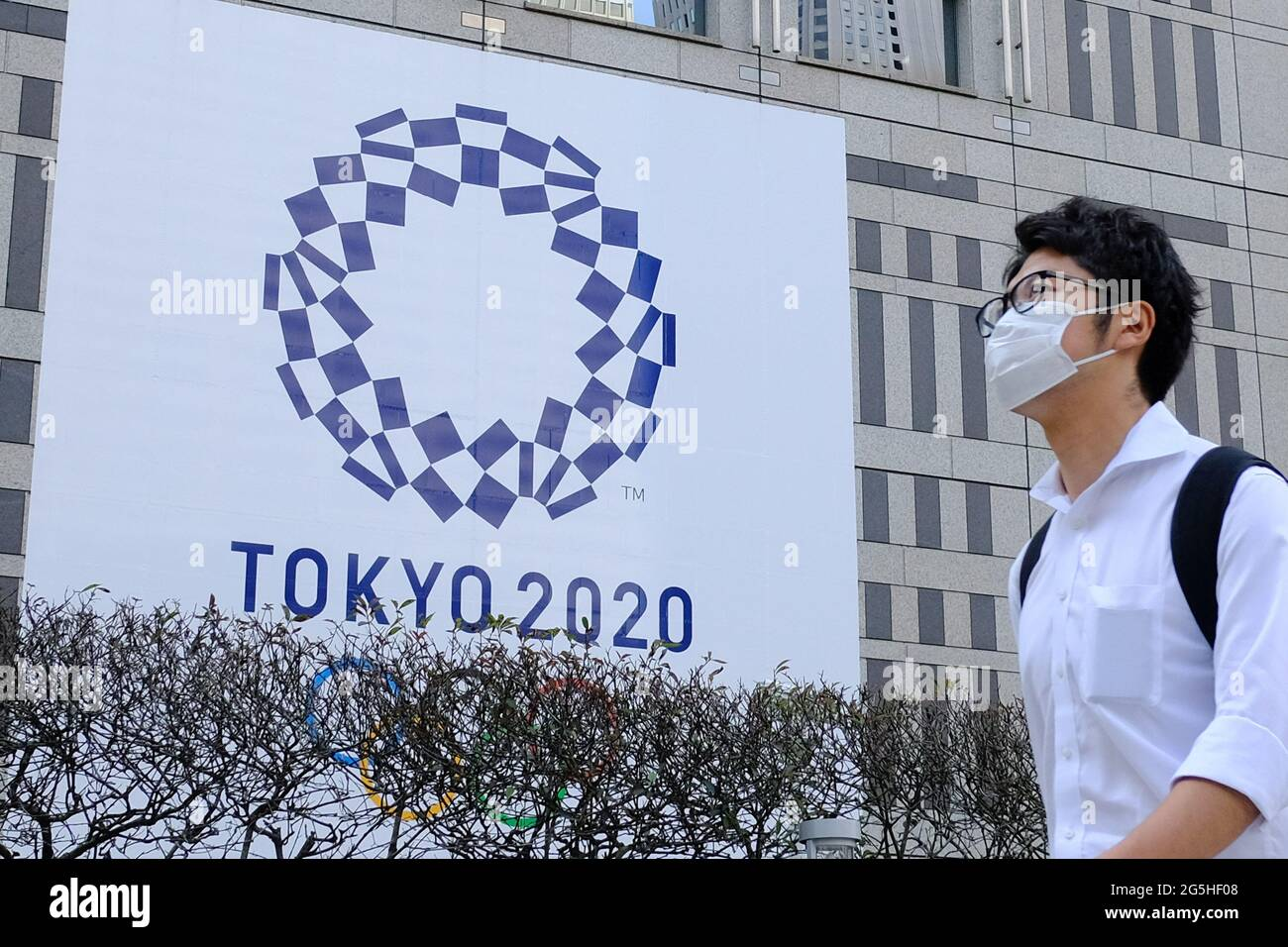 Tokyo, Japan. 25th June, 2021. A man wearing a face mask as a preventive measure against the spread of coronavirus walks past a banner for the upcoming Tokyo 2020 Olympics in front of the Tokyo Metro Government building. Credit: SOPA Images Limited/Alamy Live News Stock Photo