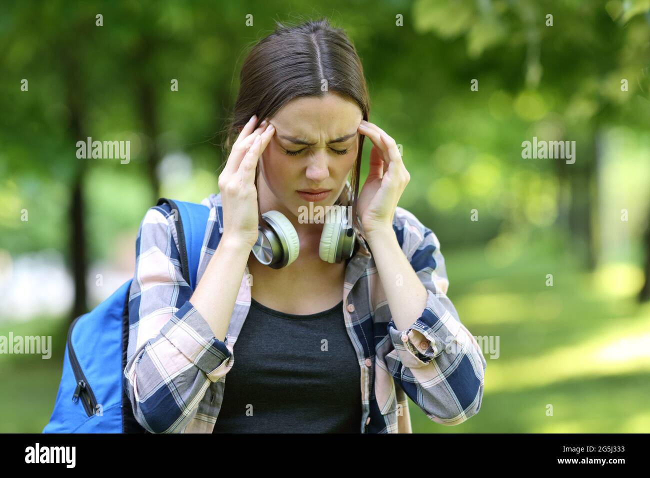 Student suffering headache walking in a park or campus on summer Stock Photo