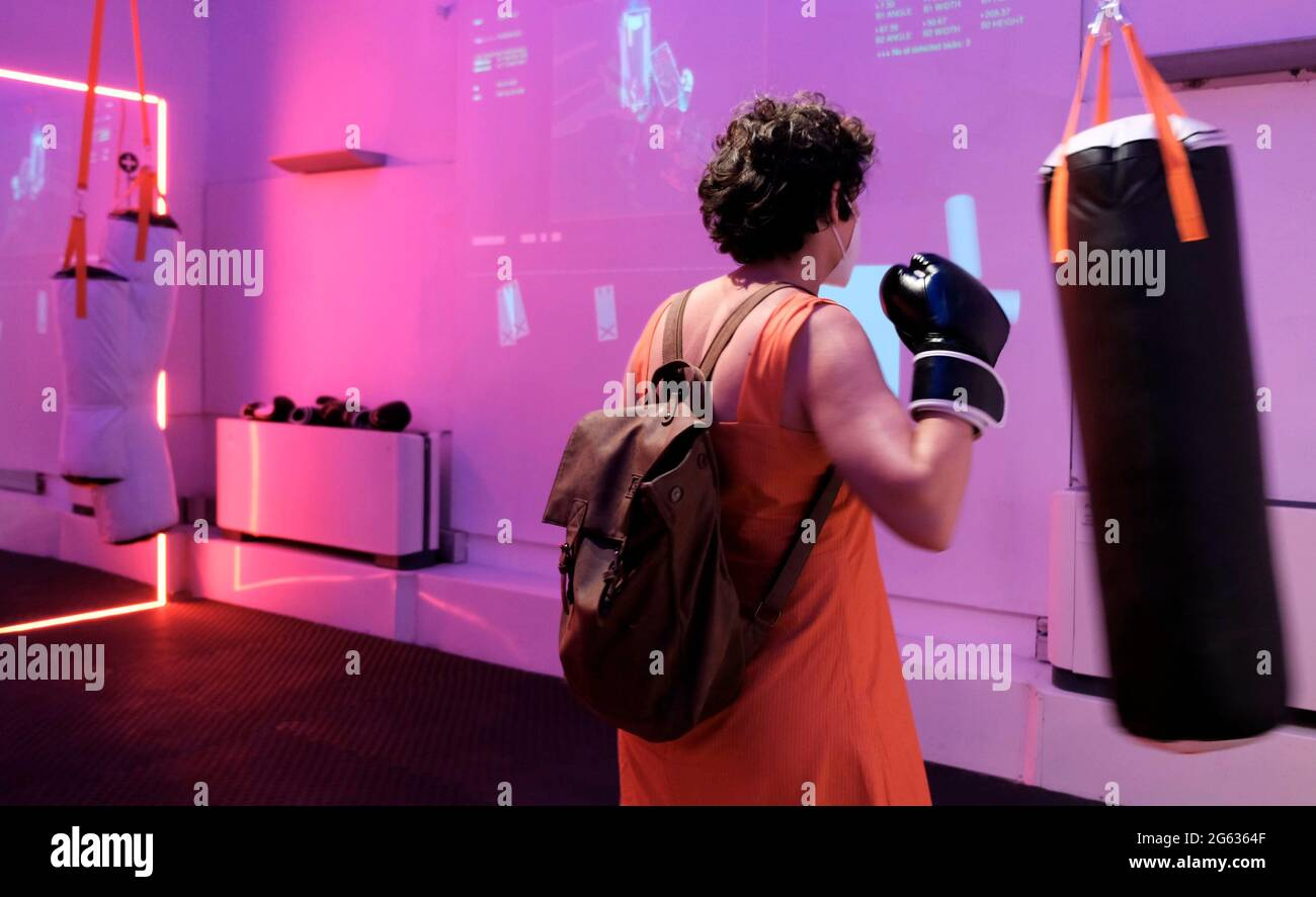 """A visitor hits a punching bag as she takes part in an active punching role through an interactive artwork entitled """"Punch. Generate. Freak"""" at the opening of the Jerusalem Design Week the city's annual celebration of creativity at Hansen House on July 01, 2021 in Jerusalem, Israel. This year's festival of local and international creativity revolves around the theme of a """"Runaway Circus"""" about the pandemic and running away from the days of virtual life toward nature, alternative culture and identities. Stock Photo"""