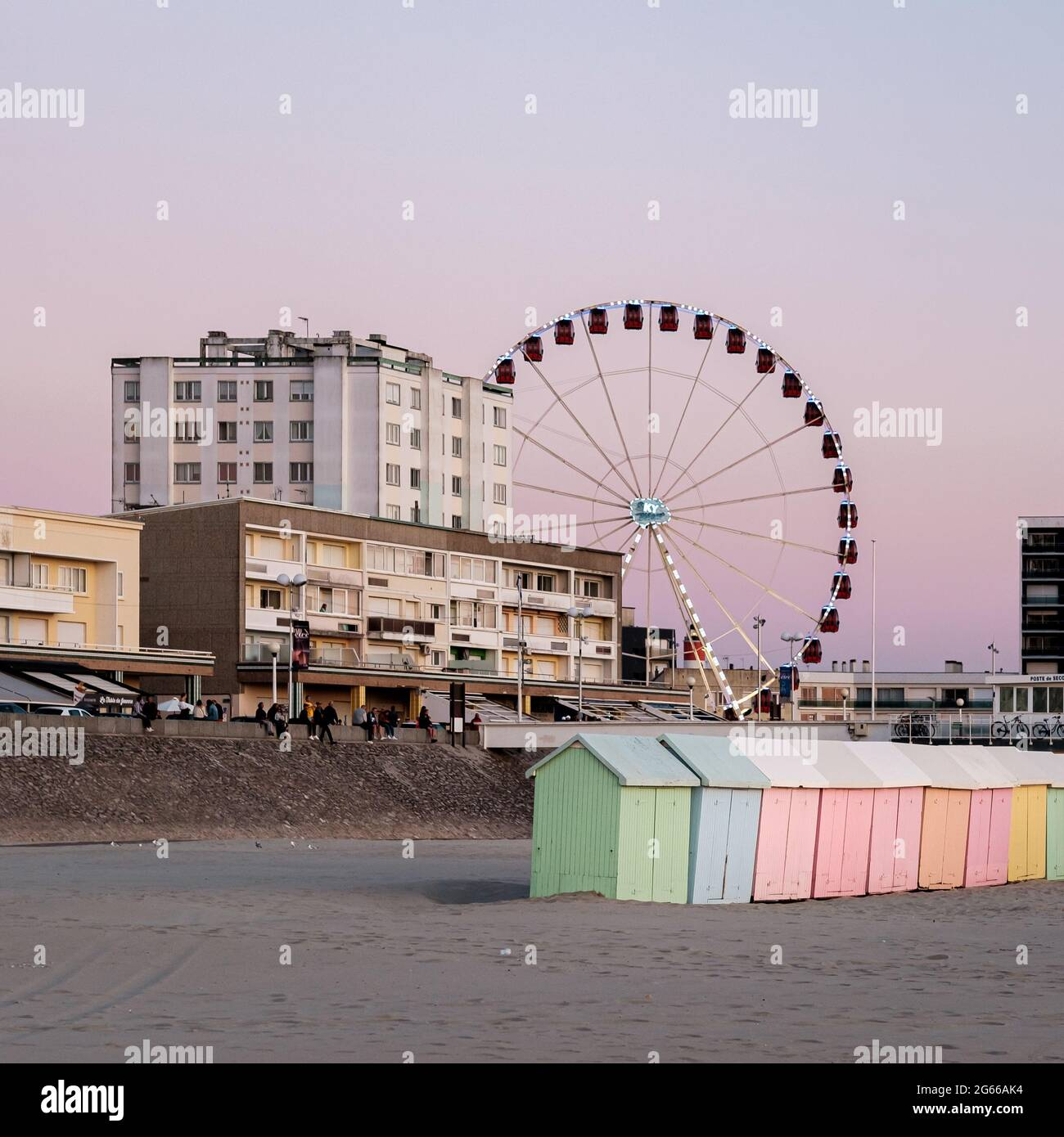 Pastel colored beach cabins and giant wheel on the beach of Berck in France Stock Photo