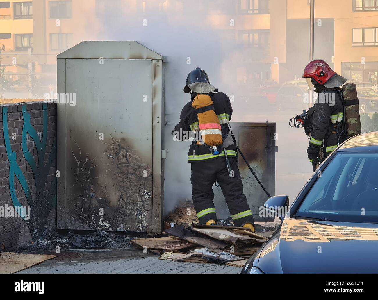 Firefighters extinguishing garbage can fire in car park Stock Photo