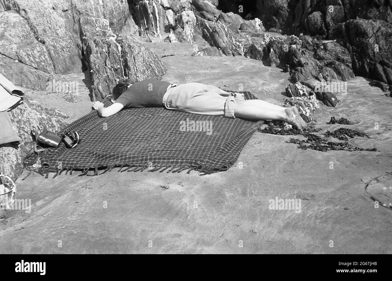 1950s, historical, a young woman with rolled-up trousers, lying face down on a rug besides some rocks on a flat, small sandy area of a beach having a rest, England, UK. Probably exhausted after building sandcastles for her children. Stock Photo