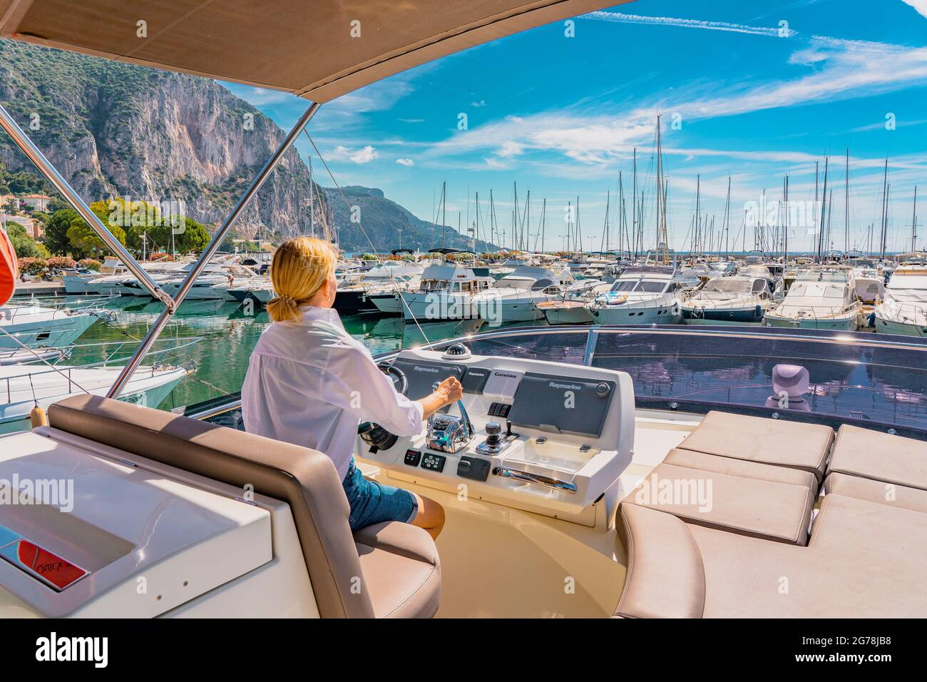 Sailing at the sea. Beautiful blond woman driving yacht. Adult woman model in a white shirt sitting at the wheel of the yacht and begin to drive luxury boat from the port. Young woman driving yacht.  Stock Photo