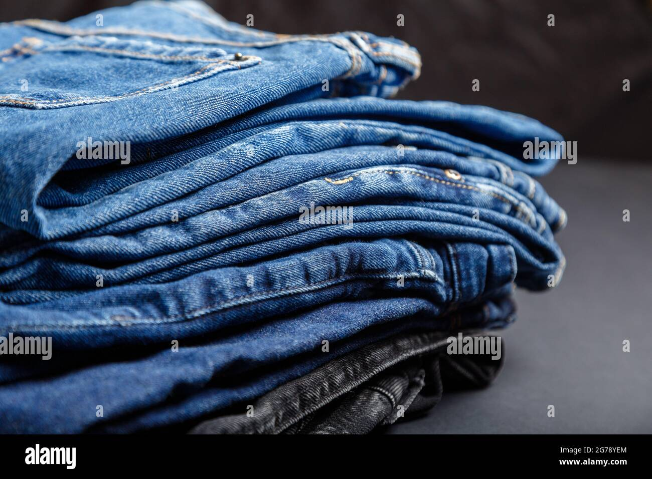Blue jeans trousers stack textile texture fabric background. Stack of variety blue color jeans, denim jean textiles on black background. Stock Photo