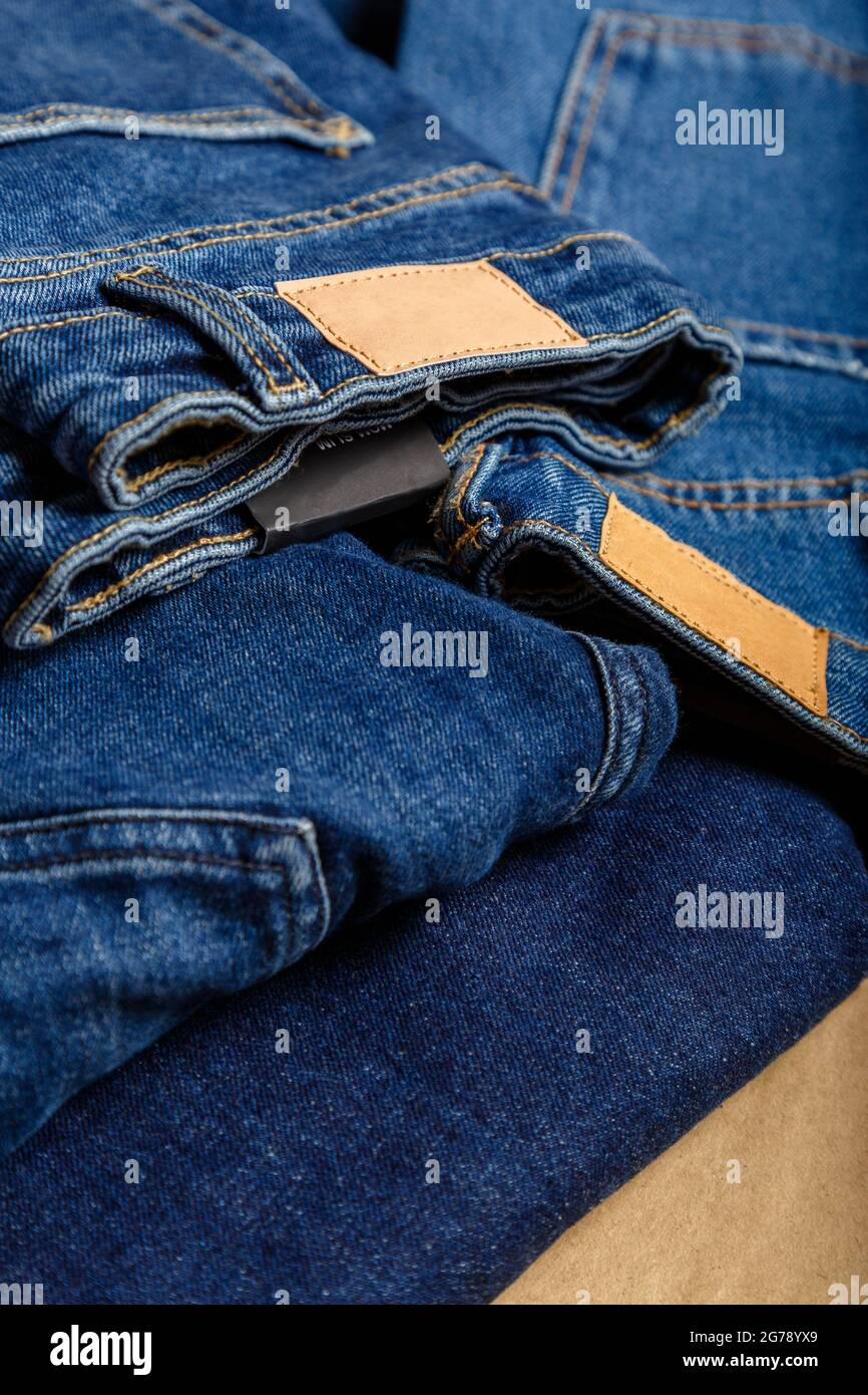 Stack of variety blue jeans, denim jean textiles as background. different blue jeans trousers stack textile texture fabric background Stock Photo