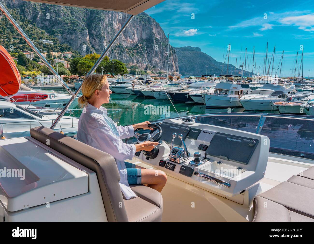 Beautiful blond woman driving yacht. Adult woman model in a white shirt sitting at the wheel of the yacht and begin to drive luxury boat from the port. Stock Photo