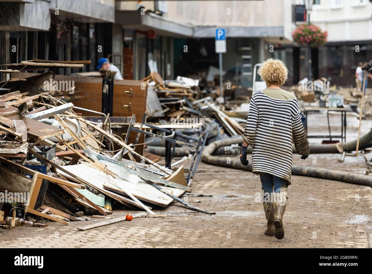 Bad Neuenahr, Germany. 16th July, 2021. A woman filthy with mud walks past a pile of rubble. Objects from a house. Massive rainfall has caused flooding in Bad Neuenahr in Rhineland-Palatinate as well as in the whole district of Ahrweiler. Credit: Philipp von Ditfurth/dpa/Alamy Live News Stock Photo