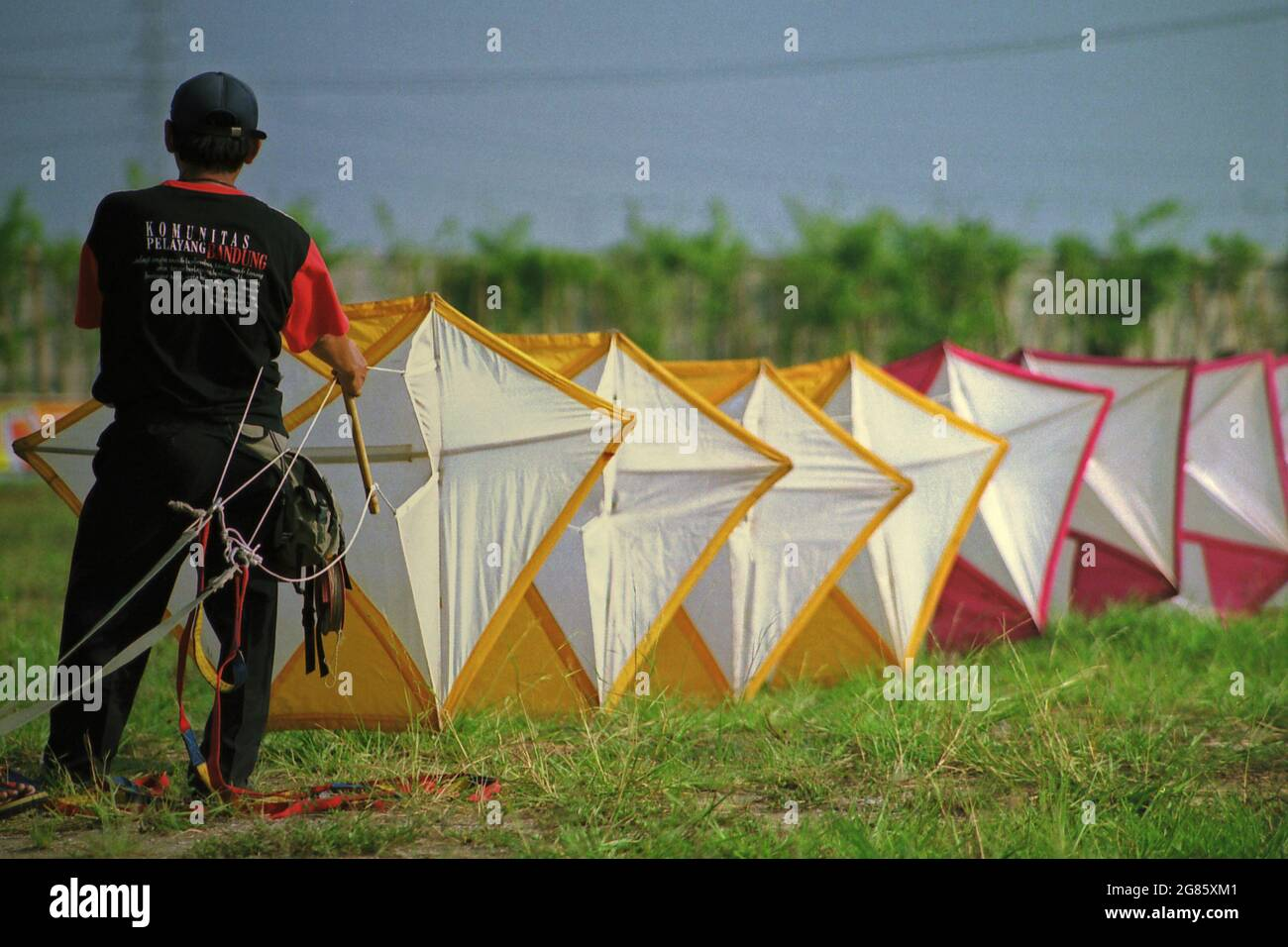 A man preparing a giant kite during the 2004 Jakarta International Kite Festival that held on July 9-11 at Carnival Beach in Ancol Dreamland, North Jakarta, Jakarta, Indonesia. Stock Photo