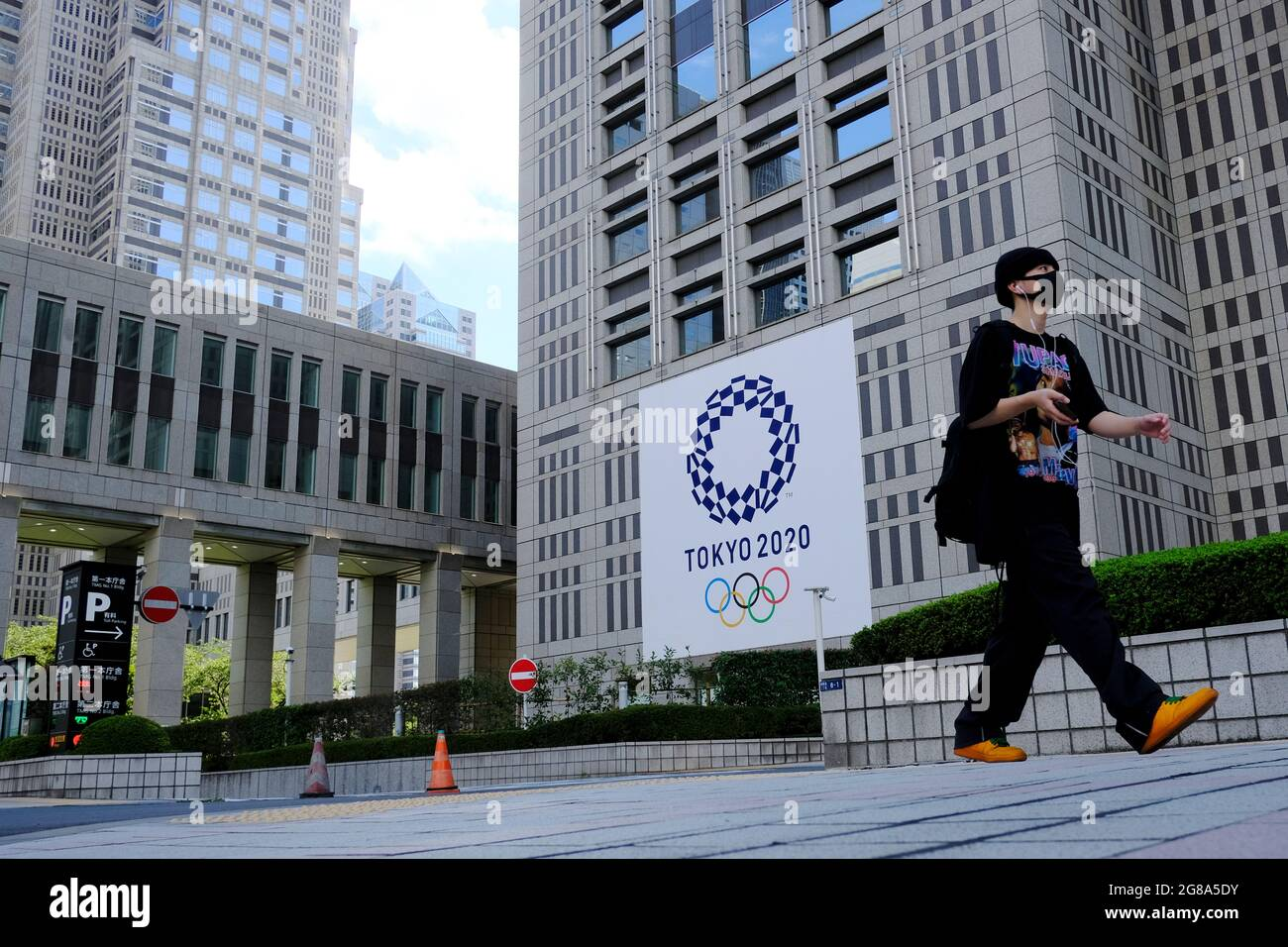 A man wearing a face mask as a preventive measure against the spread of coronavirus walks past a banner for the upcoming Tokyo 2020 Olympics in front of the Tokyo Metro Government building. (Photo by James Matsumoto / SOPA Images/Sipa USA) Stock Photo