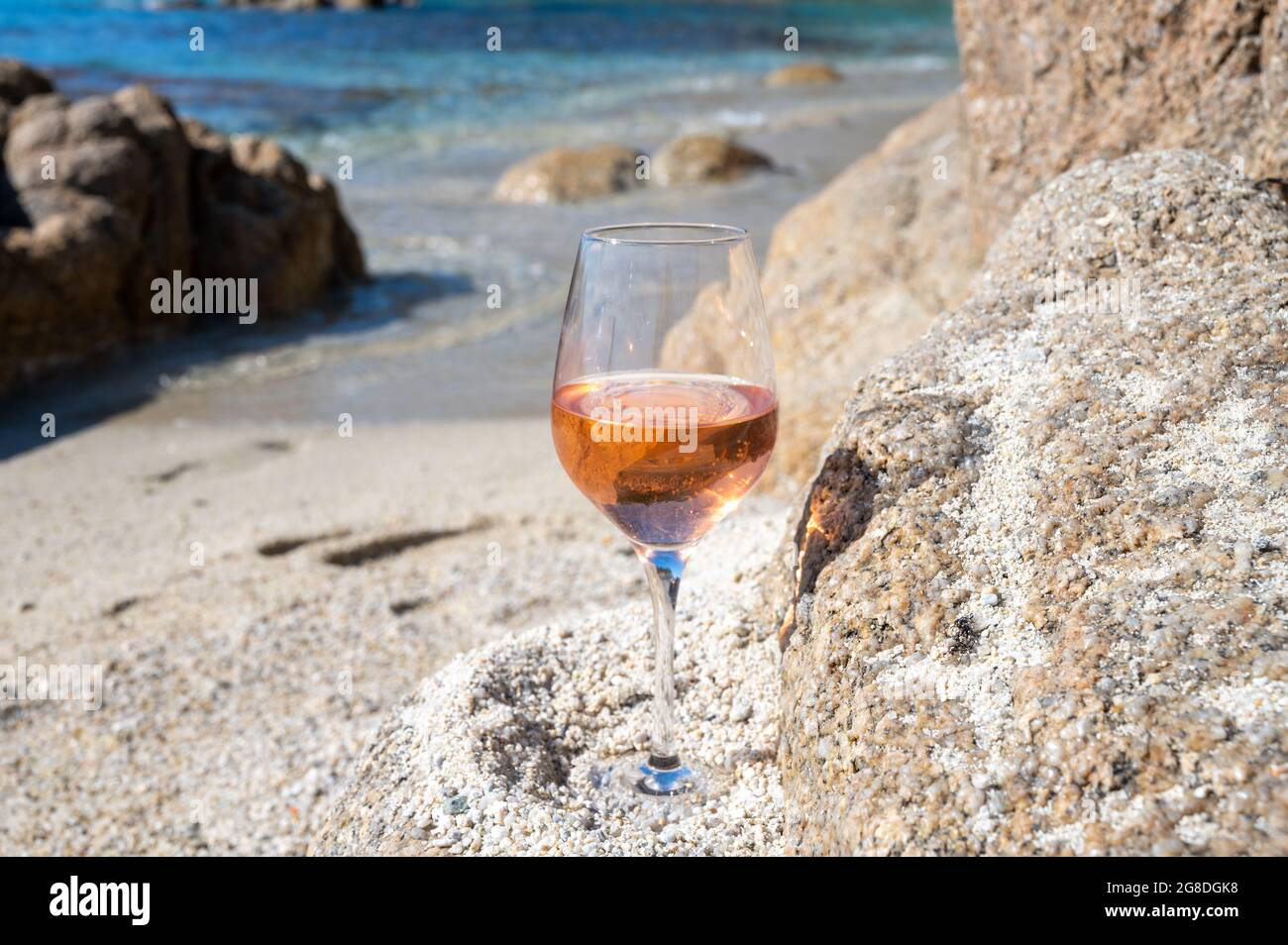 Summer time in Provence, glass of cold rose wine on sandy beach near Saint-Tropez in sunny day, Var department, France Stock Photo