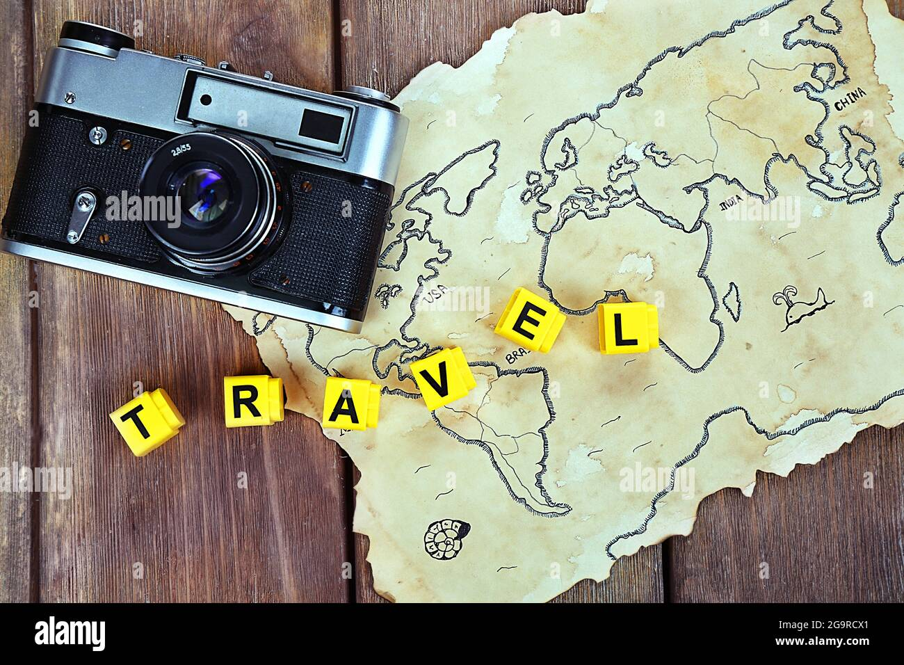 Retro camera on world map with word Travel on wooden table background Stock Photo