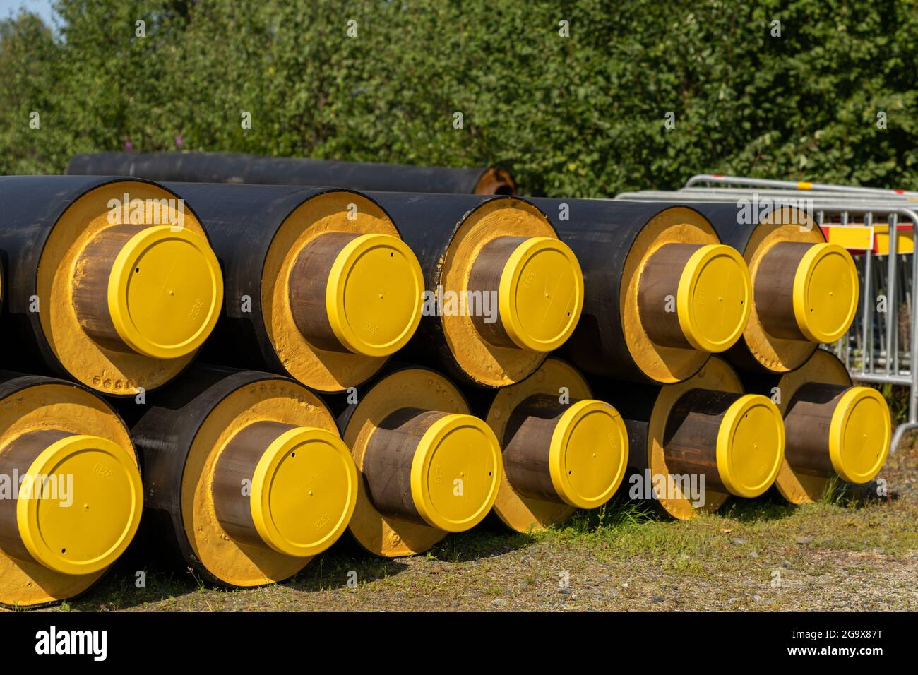A close up view of a stack of large industrial water pipes with thick insulation covering for building in cold regions Stock Photo