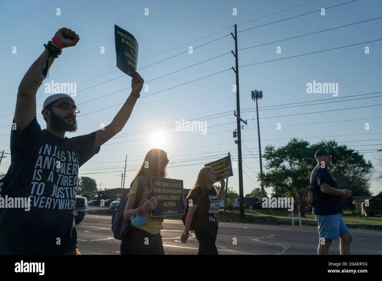 Austin, Texas USA, July 30, 2021: Voting rights activists march along an interstate highway frontage road toward the Texas Capitol from north Austin on the third day of a 30-mile journey protesting Republican efforts to suppress votes nationwide and in Texas. Shifts of marchers trade off in an effort to combat oppressive Texas heat. Credit: Bob Daemmrich/Alamy Live News Stock Photo