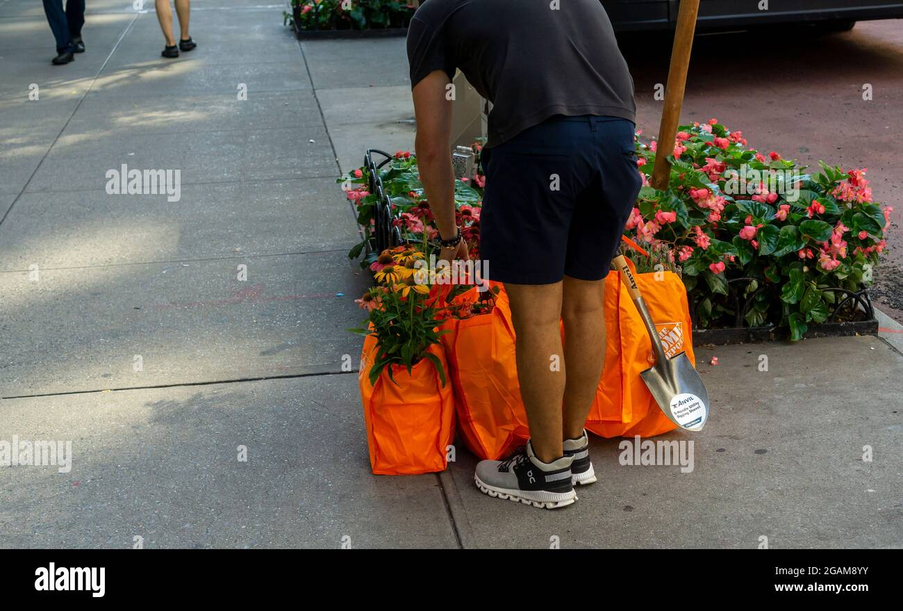 Shopper with his Home Depot gardening purchses in busy Chelsea in New York on Friday, July 30, 2021. (© Richard B. Levine) Stock Photo