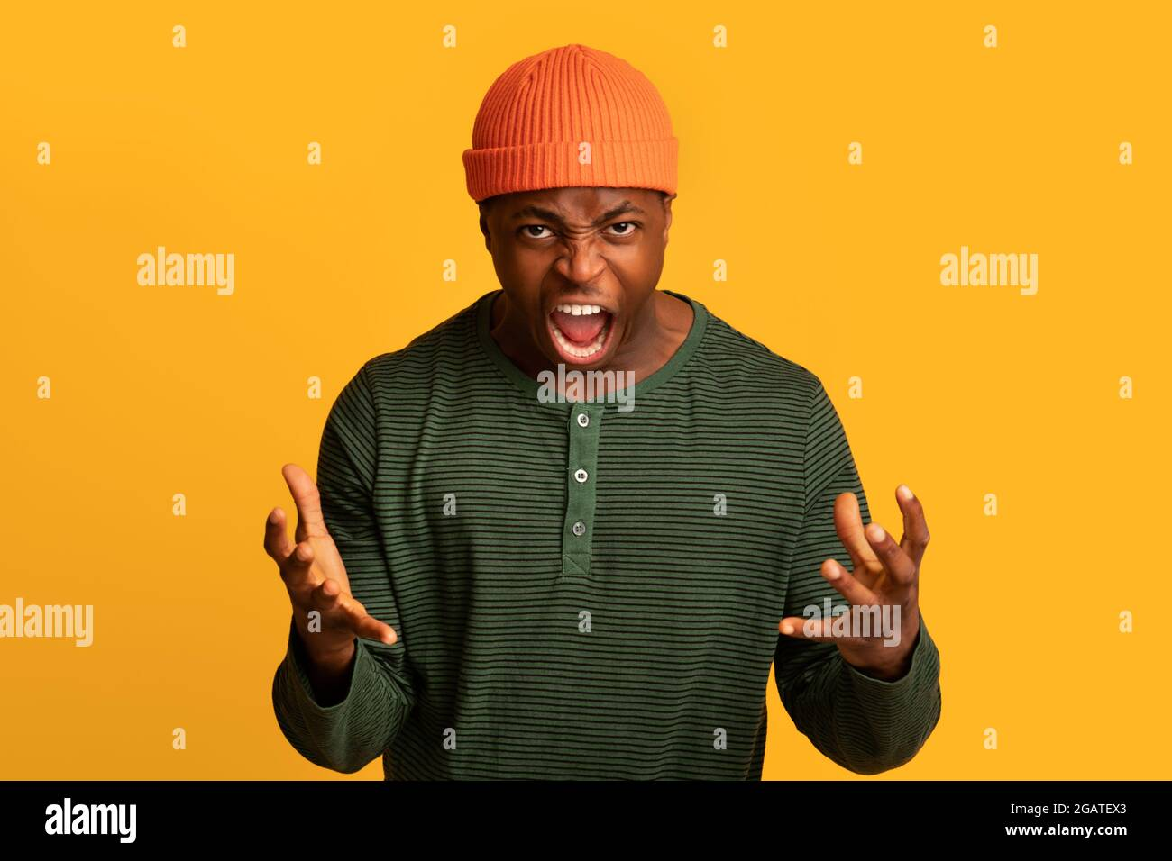 Portrait of furious african american guy shouting with rage at camera, very angry black man raising hands and screaming with fury while standing isola Stock Photo
