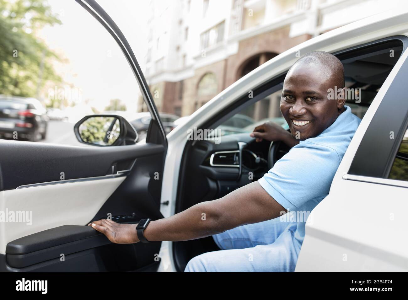 Cheerful black guy getting into nice automobile Stock Photo
