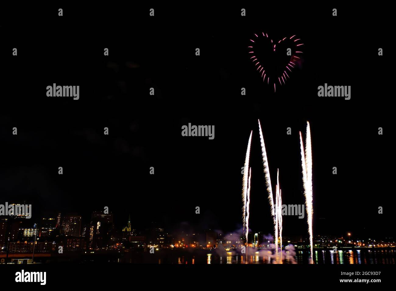 Heart shaped fireworks sideways over a city skyline at night. Other fireworks rise towards the heart. Stock Photo