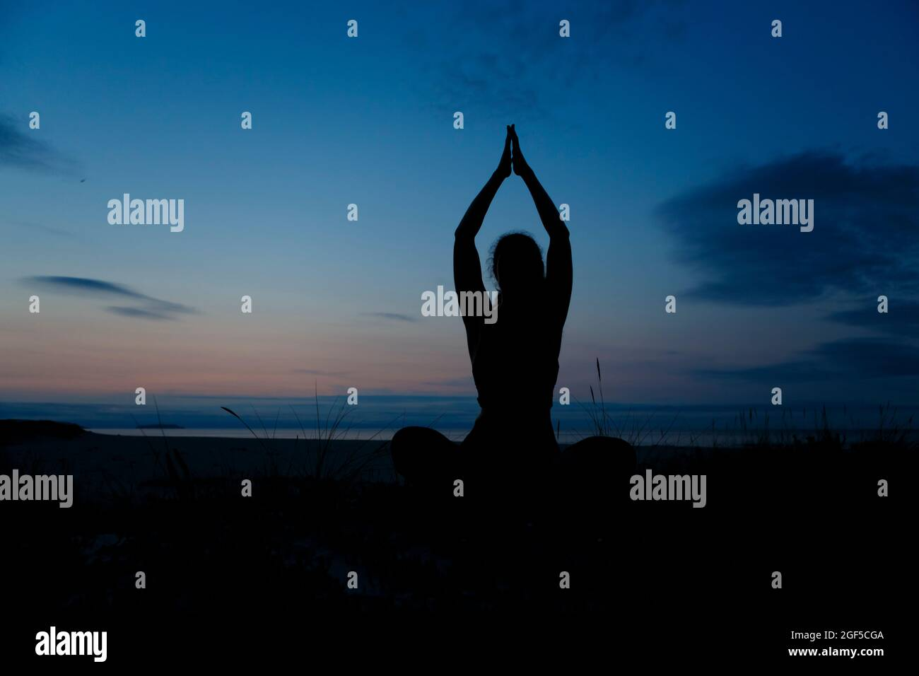 Silhouette of young woman practicing yoga, lotus position, and meditating on the beach Stock Photo